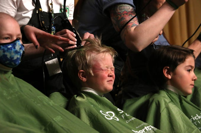 8 year old Wyatt Stockert, middle, suffers through his hair cut during the Northern Nevada Children Cancer Foundation and the St. Baldrick's Foundation's fundraising head-shaving event at the Downtown Reno Ballroom on March 15, 2019.