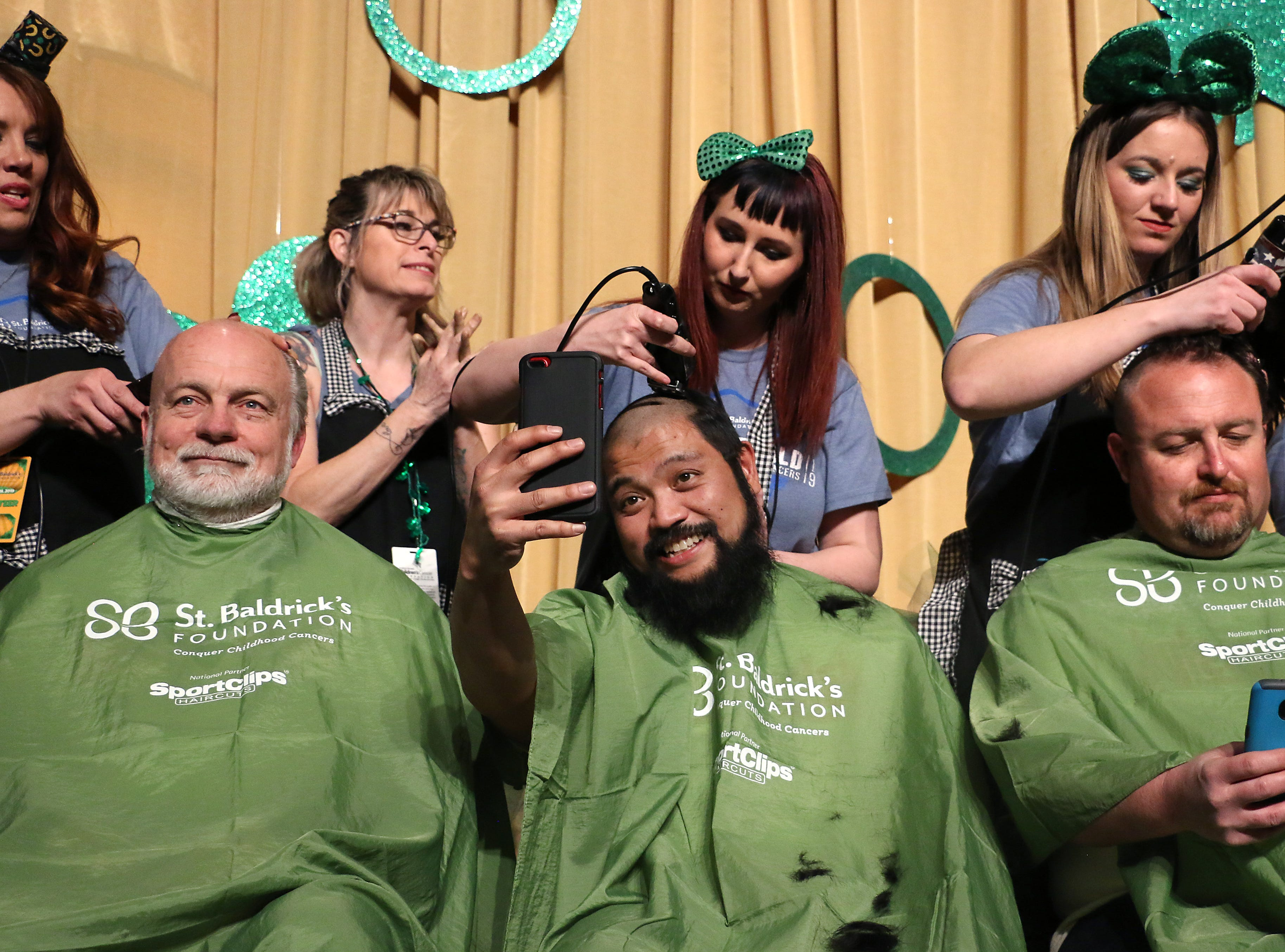 Patrick Molino, middle, takes a selfie during the Northern Nevada Children Cancer Foundation and the St. Baldrick's Foundation's fundraising head-shaving event at the Downtown Reno Ballroom on March 15, 2019.