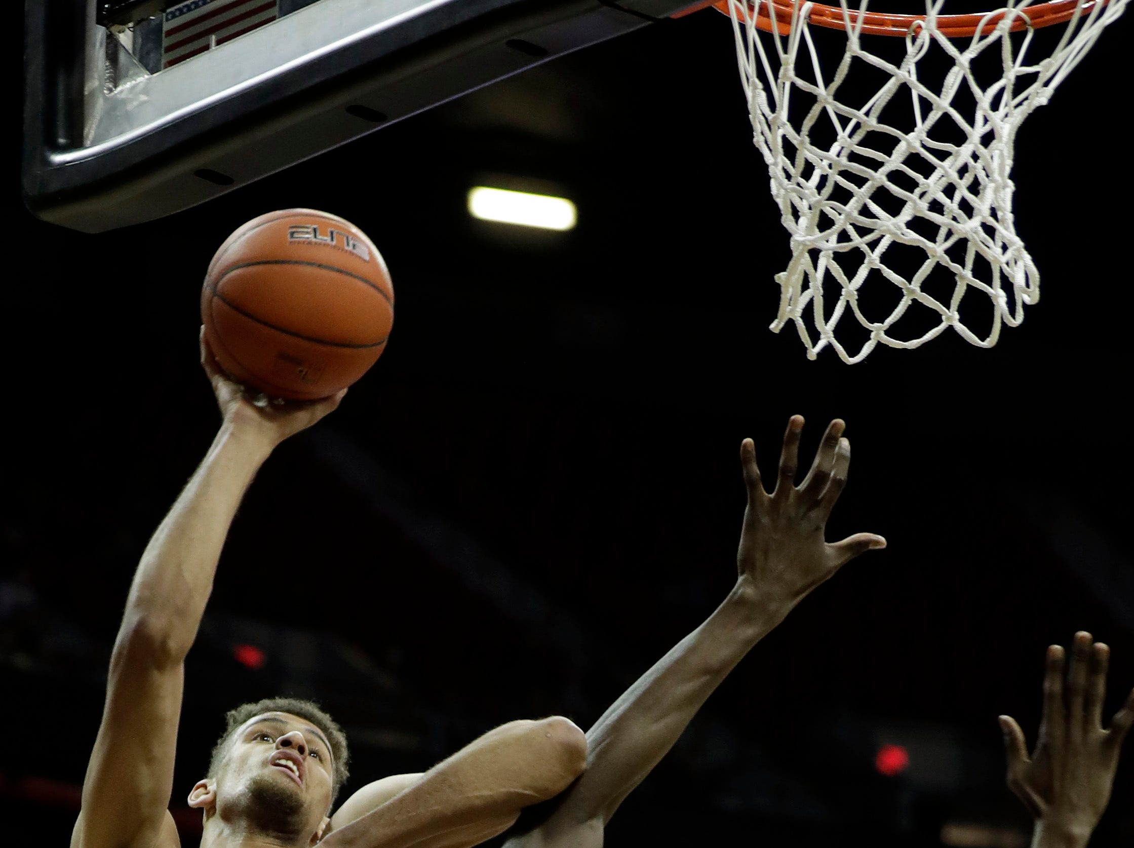 San Diego State's Nathan Mensah (31) defends as Nevada's Trey Porter shoots during the first half of an NCAA college basketball game in the Mountain West Conference men's tournament Friday, March 15, 2019, in Las Vegas. (AP Photo/Isaac Brekken)
