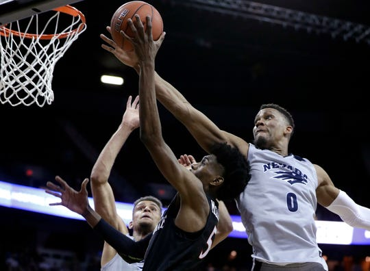 Nevada's Tre'Shawn Thurman looks to block a shot from San Diego State's Jalen McDaniels during the second half of Friday's Mountain West Tournament game.
