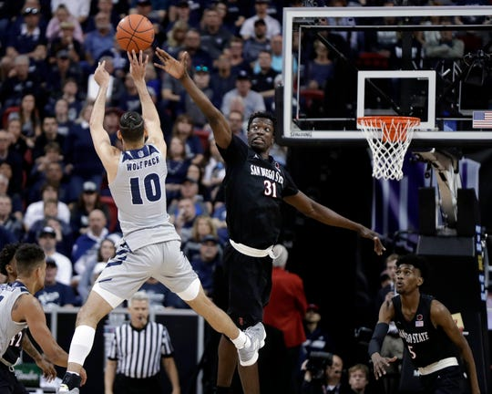 San Diego State's Nathan Mensah defends as Nevada's Caleb Martin shoots during the second half of an NCAA college basketball game in the Mountain West Conference men's tournament Friday, March 15, 2019, in Las Vegas. (AP Photo/Isaac Brekken)