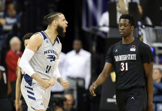 Nevada's Cody Martin reacts after scoring against Nathan Mensah and San Diego State during Friday's semifinal game.