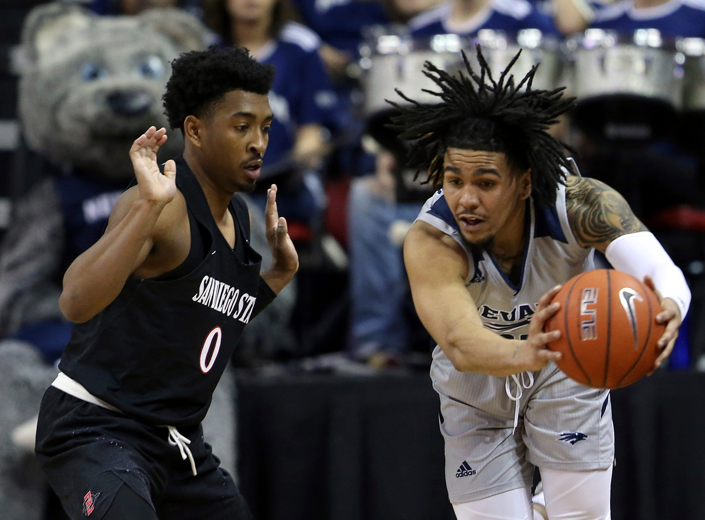 San Diego State's Devin Watson (0) defends as Nevada's Jazz Johnson (22) reaches to catch a pass during the second half of the team's NCAA college basketball game in the Mountain West Conference men's tournament Friday, March 15, 2019, in Las Vegas. (AP Photo/Isaac Brekken)