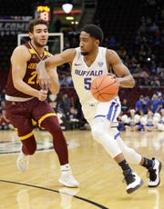 Buffalo's CJ Massinburg (5) drives past Central Michigan's Kevin McKay (20) during the first half of an NCAA college basketball game in the semifinals of the Mid-American Conference men's tournament Friday, March 15, 2019, in Cleveland.