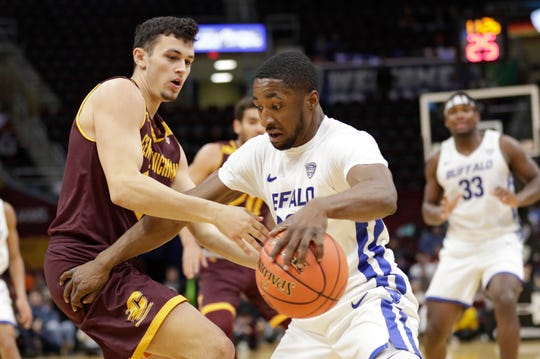 Buffalo's Dontay Caruthers, right, drives past Central Michigan's Matt Beachler during the first half of an NCAA college basketball game in the semifinals of the Mid-American Conference men's tournament Friday, March 15, 2019, in Cleveland.