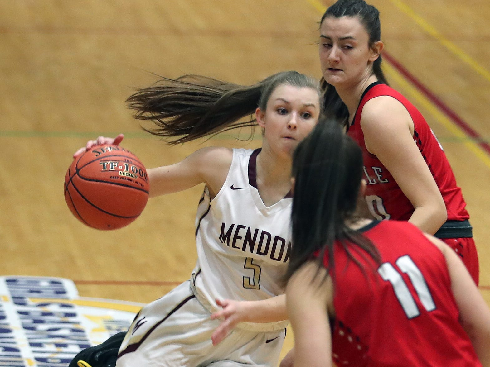 Pittsford Mendon's Courtney Naugle (5) drives to the basket in front Jamesville-DeWitt defenders during the girls Class A state semifinal at Hudson Valley Community College in Troy March 16, 2019.