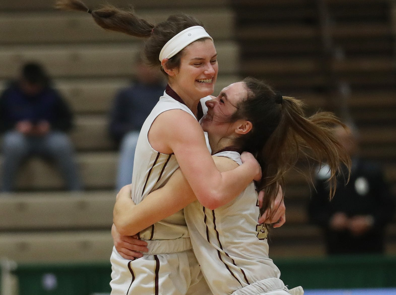 Pittsford Mendon's Katie Bischoping (31) and Ellie Mooney (3) celebrate their victory over  Jamesville-DeWitt in the girls Class A state semifinal at Hudson Valley Community College in Troy March 16, 2019. Pittsford Mendon won 44-32.