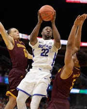 Buffalo's Dontay Caruthers (22) drives to the basket between Central Michigan's Larry Austin Jr. (0) and Robert Montgomery (5) during the second half of an NCAA college basketball game in the semifinals of the Mid-American Conference men's tournament Friday, March 15, 2019, in Cleveland. Buffalo won 85-81.