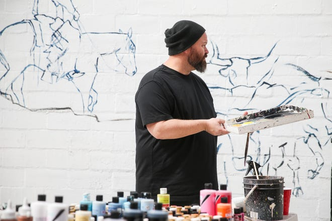 """Justin Blair paints a mural based on the movie """"Giant"""" Saturday, March 16, 2019, in Paintbrush Alley."""