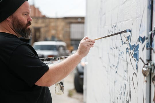 "Justin Blair paints a mural based on the movie ""Giant"" Saturday, March 16, 2019, in Paintbrush Alley."