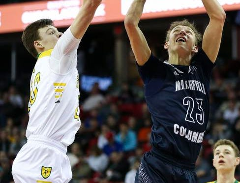 Columbus Catholic High School's Bryce Fuerlinger (23) puts up a shot as Sheboygan Area Lutheran High School's Jacob Ognacevic (23) defends the basket in the Division 5 boys basketball state championship game on Saturday, March 16, 2019, at the Kohl Center in Madison, Wis. The Crusaders beat Columbus Catholic, 74-61.