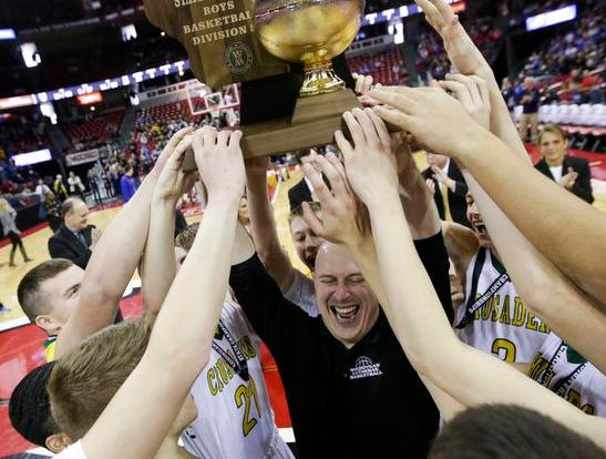 Sheboygan Area Lutheran coach Nick Verhagen and his players celebrate after winning the Division 5 state title with a 77-69 victory over Marshfield Columbus on Saturday.