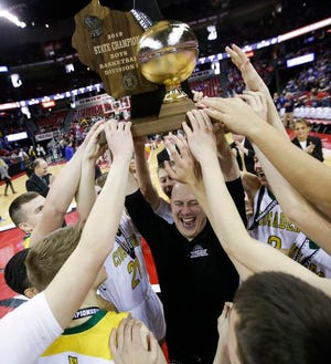 Sheboygan Lutheran coach Nick Verhagen and his players celebrate after winning the Division 5 state title with a 77-69 victory over Marshfield Columbus on Saturday.