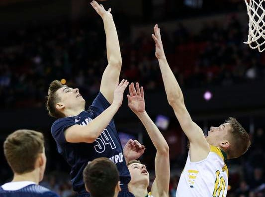 Columbus Catholic High School's Ethan Meece (34) puts up a shot over Sheboygan Area Lutheran High School's Graden Grabowski (10) in the Division 5 boys basketball state championship game on Saturday, March 16, 2019, at the Kohl Center in Madison, Wis. The Crusaders beat Columbus Catholic, 74-61.