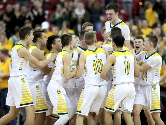Sheboygan Lutheran players celebrate after the Crusaders beat Columbus Catholic to win the WIAA Division 5 boys basketball state championship Saturday at the Kohl Center in Madison.