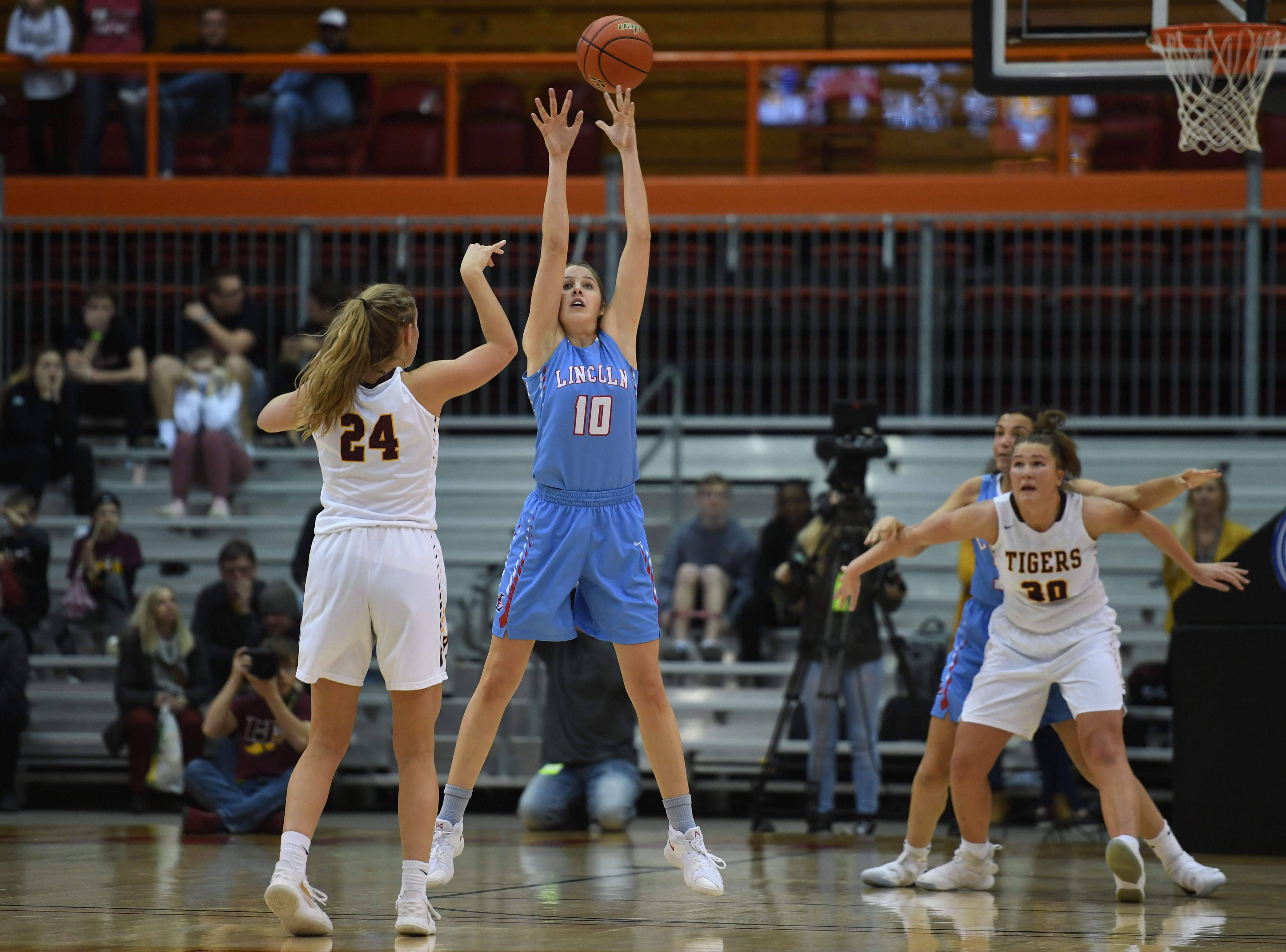 Lincoln's Morgan Hansen attempts to break up a pass between Harrisburg's Aby Phipps (24) and Jeniah Ugofsky during the game in the Class AA semifinals Thursday, March 15, in Rapid City.