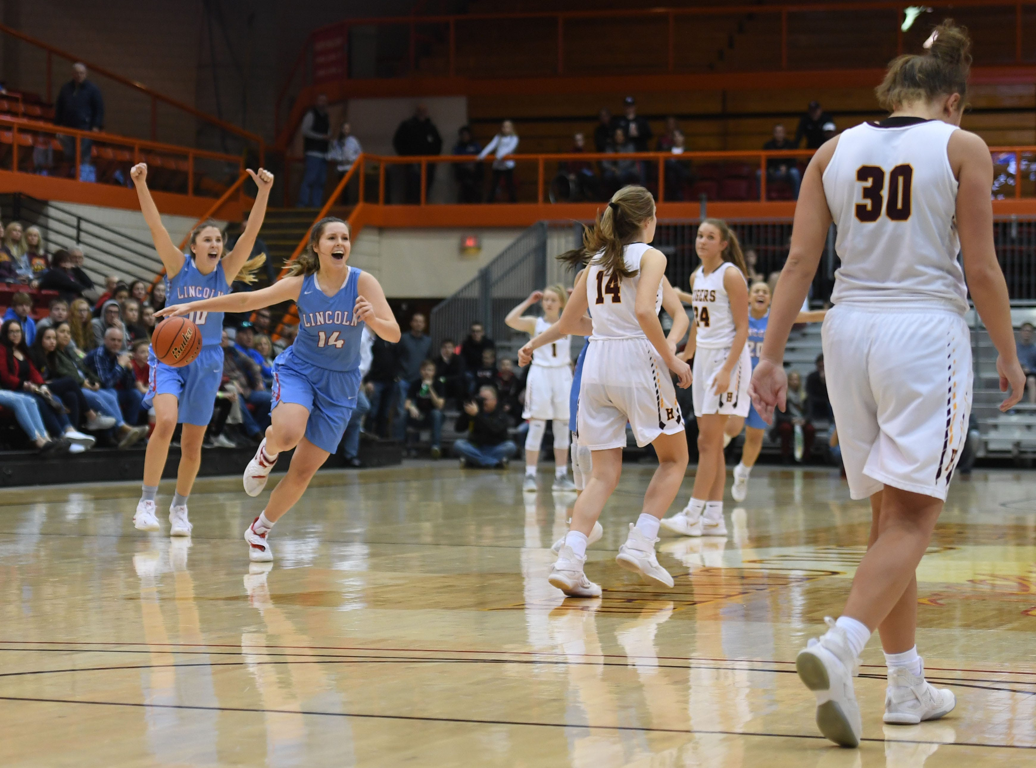 Lincoln's Morgan Hansen and Emma Osmundson run off the court after their win against Harrisburg in the Class AA semifinals Thursday, March 15, in Rapid City.