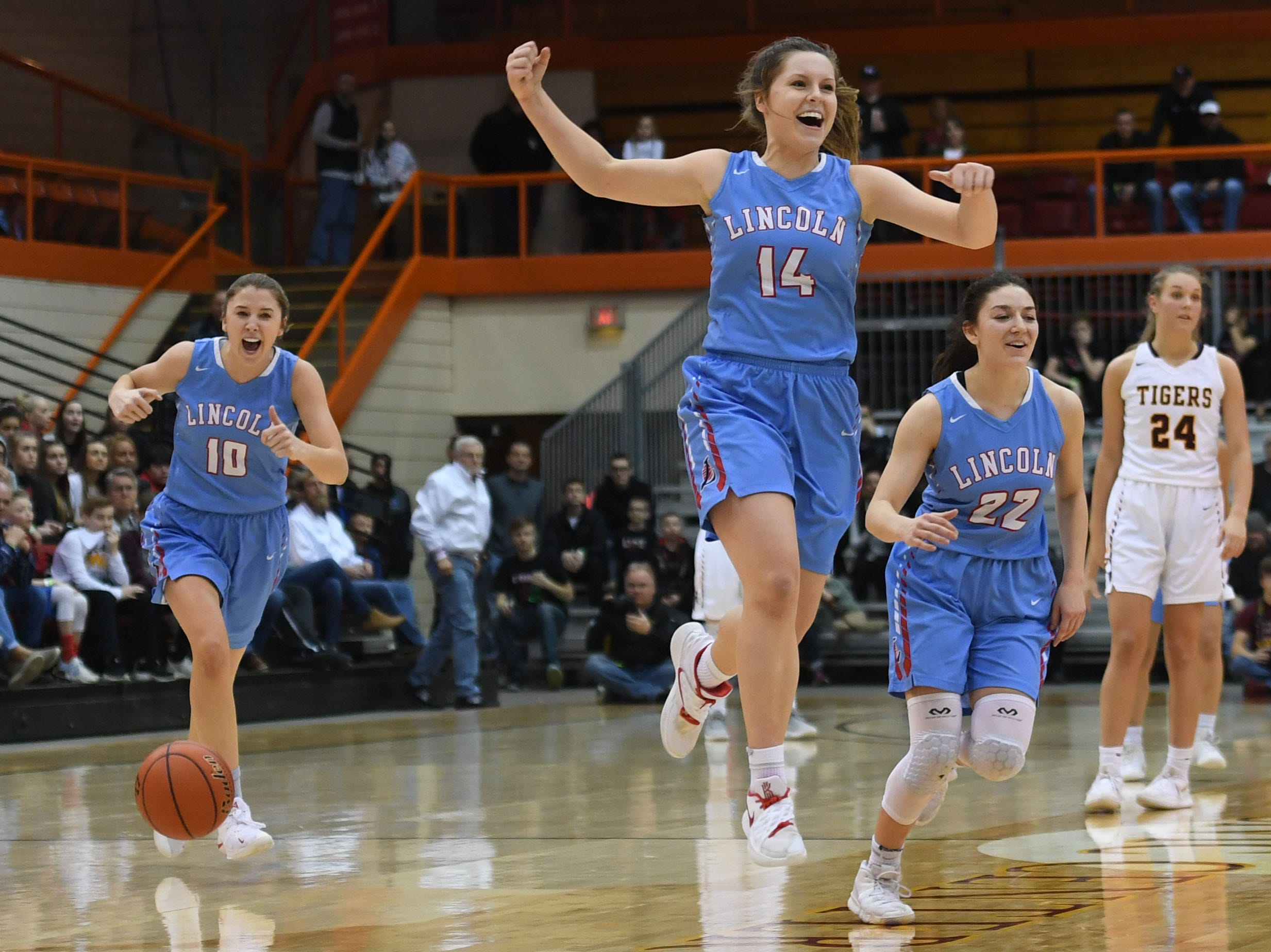 Lincoln's Morgan Hansen (10), Emma Osmundson (14) and  Brooke Brown (22) run off the court after their win against Harrisburg in the Class AA semifinals Thursday, March 15, in Rapid City.