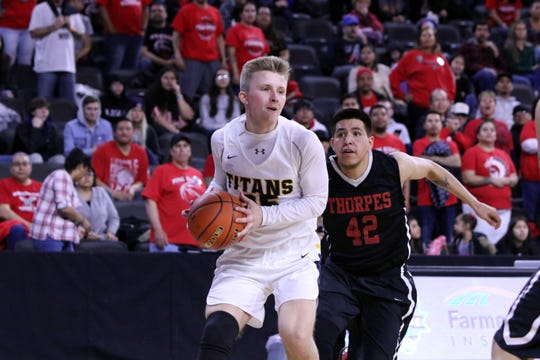 Mason Ritter of Tea Area drives to the basket as Halin Bad Bear of Pine Ridge defends during Friday's semifinal game at the Premier Center.
