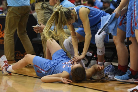 Lincoln teammates pretend to resuscitate each other after a three pointer in the fourth period of the game against Harrisburg in the Class AA semifinals Thursday, March 15, in Rapid City.