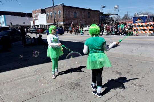 Lyla, 12, and 11-year-old Sophie Holmes play with bubbles along the St. Patrick's Day parade route.
