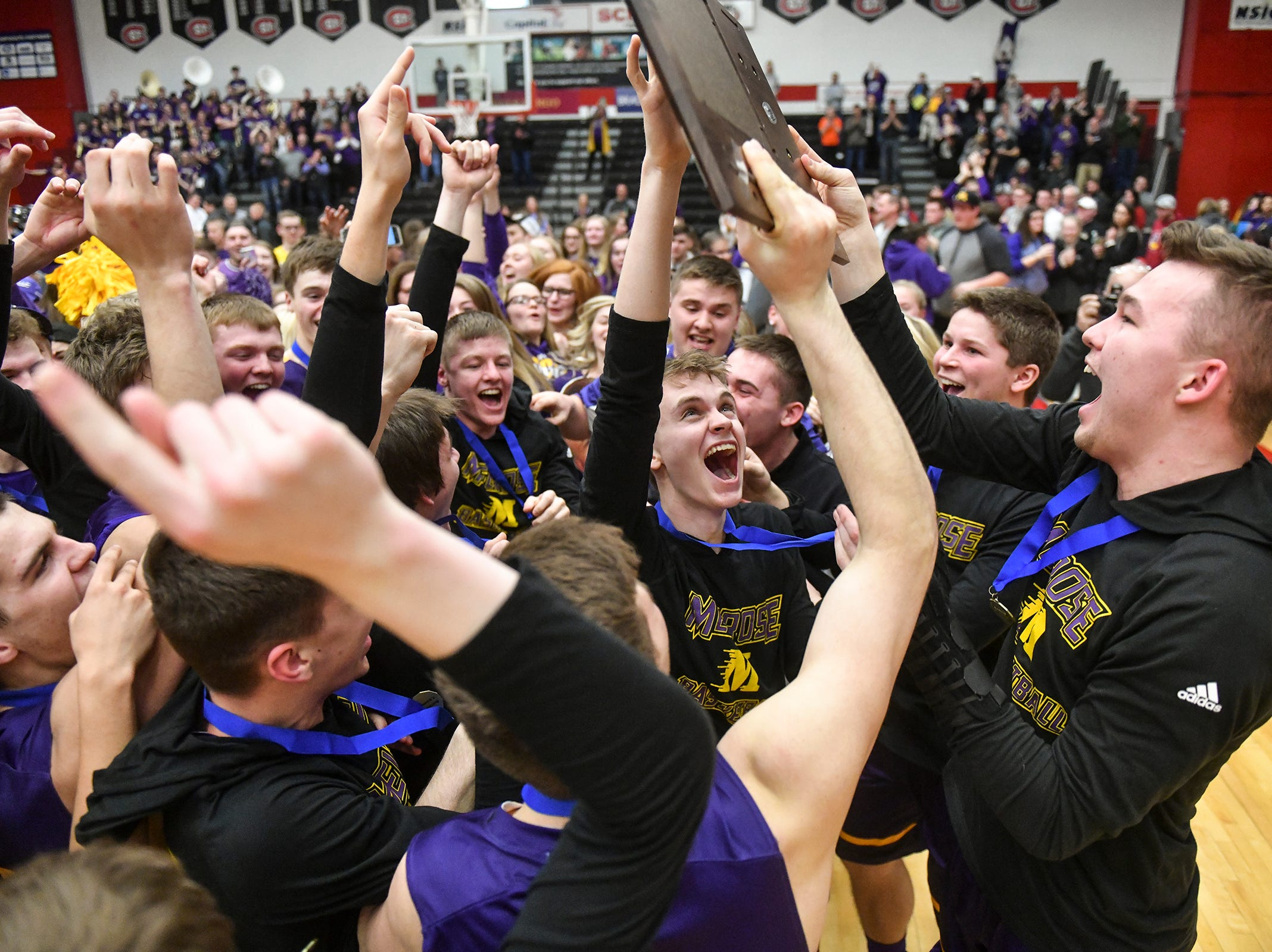 Melrose players celebrate with their first place trophy after a 52-51 win against Albany Friday, March 15, following Section 6-2A championship game at Halenbeck Hall in St. Cloud.