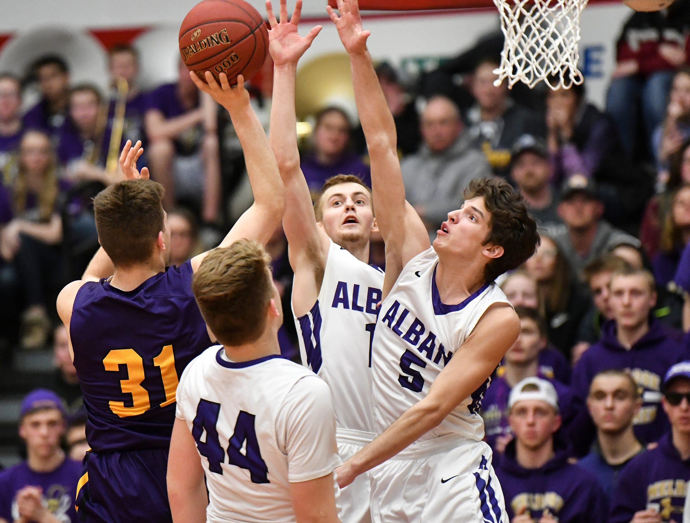 Albany players jump to block a shot by Adam Helmin of Melrose during the second half of the Friday, March 15, Section 6-2A championship game at Halenbeck Hall in St. Cloud.