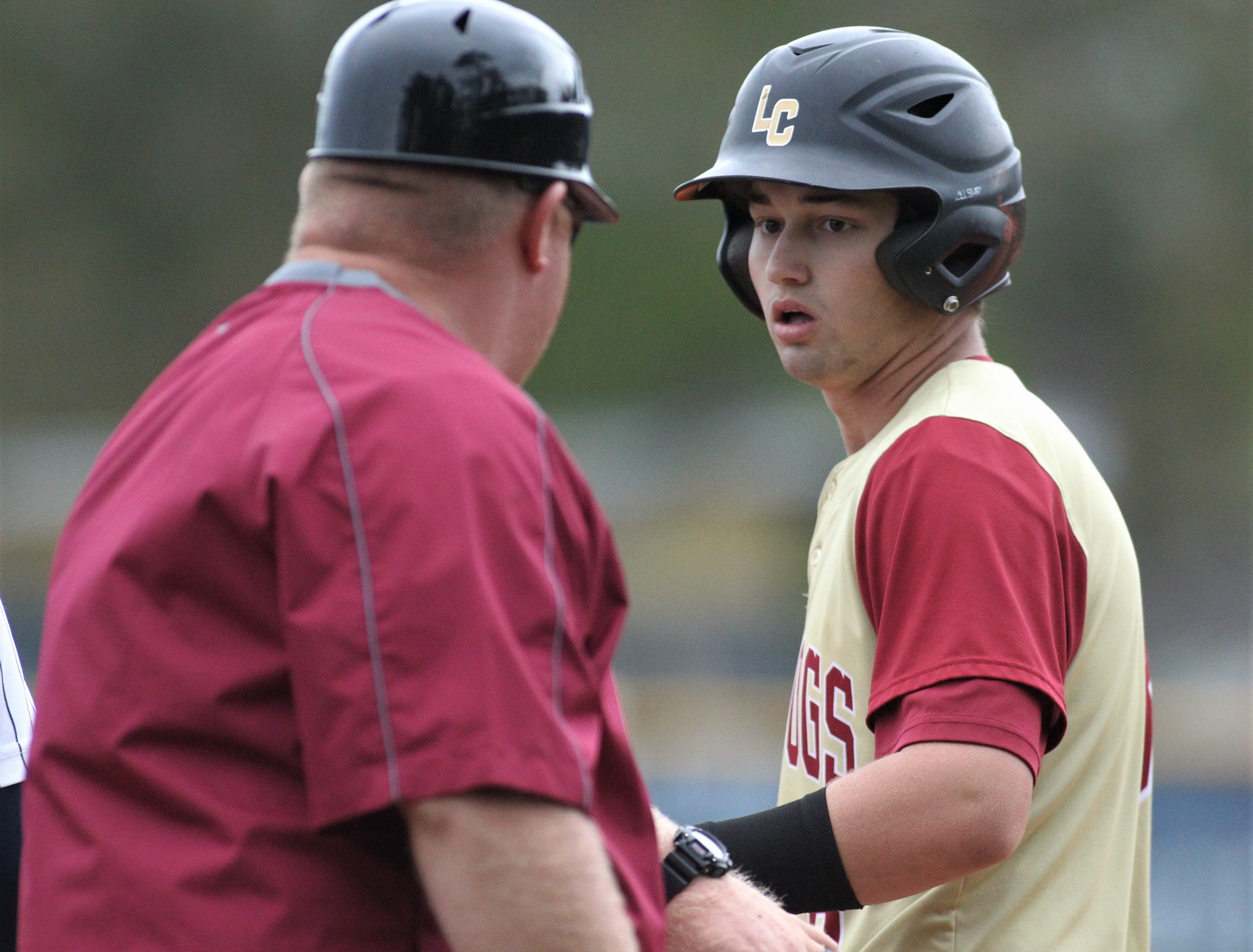 Liberty County's Hunter Sanford gets congratulated after a hit by first base coach Randall Crum as Liberty County's baseball team went on the road to beat Maclay 8-2 on Saturday, March 16, 2019. The Bulldogs played their first game following their head coach Corey Crum's tragic death six days ago.