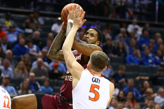 Florida State Seminoles forward Phil Cofer (0) shoots the ball against Virginia Cavaliers guard Kyle Guy (5) in the first half in the ACC conference tournament at Spectrum Center.
