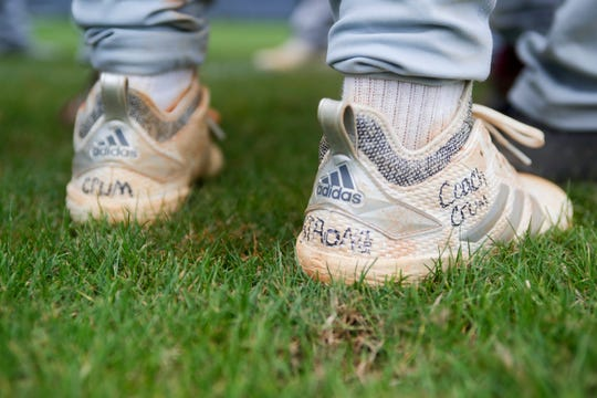 "Liberty County baseball player Charlie Burns (6) wears cleats reading ""Crum strong"" and ""Coach Crum"" during a game against Maclay on March  16, 2019 following the death of their coach Corey Crum, who was electrocuted along with his wife while installing a new scoreboard after Hurricane Michael destroyed the program's old one."