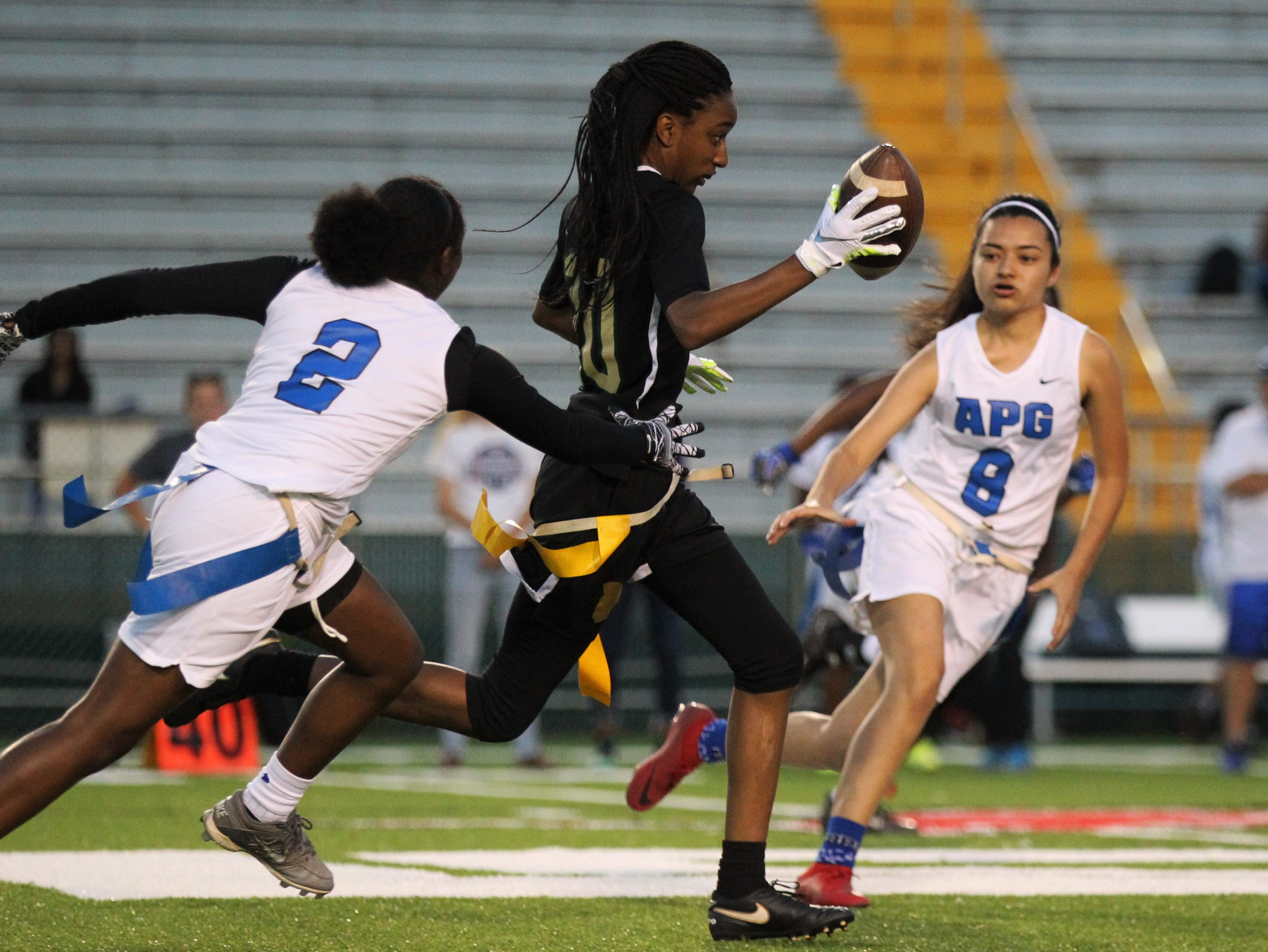 Lincoln senior Kayley Farmer splits would-be flag pullers for a long punt return as Godby's flag football team beat Lincoln 25-6 at Gene Cox Stadium on March 14, 2019.