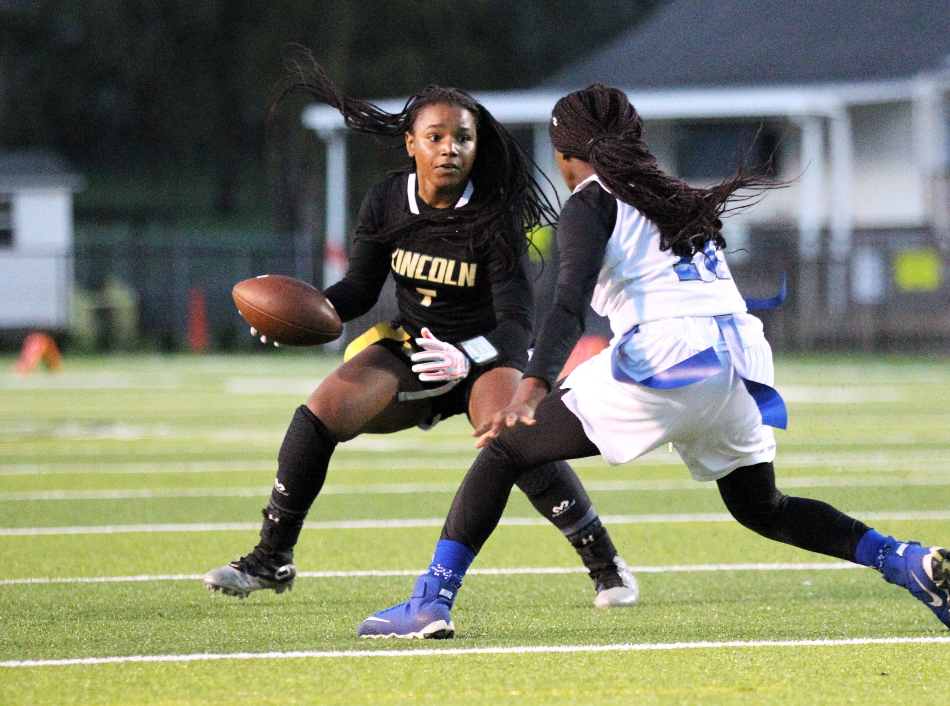 Lincoln sophomore Erin Turral tries to evade Godby's Essence Nobles as Godby's flag football team beat Lincoln 25-6 at Gene Cox Stadium on March 14, 2019.