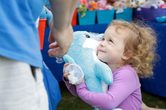 Gabriella Hansen squeezes her new dolphin that she just stuffed at a booth hosted by A Zoo Stuffed by You. A hundred vendors set up booths outside the Tallahassee Automobile Museum for the inaugural Capital Craft Fest Saturday, March 16, 2019.