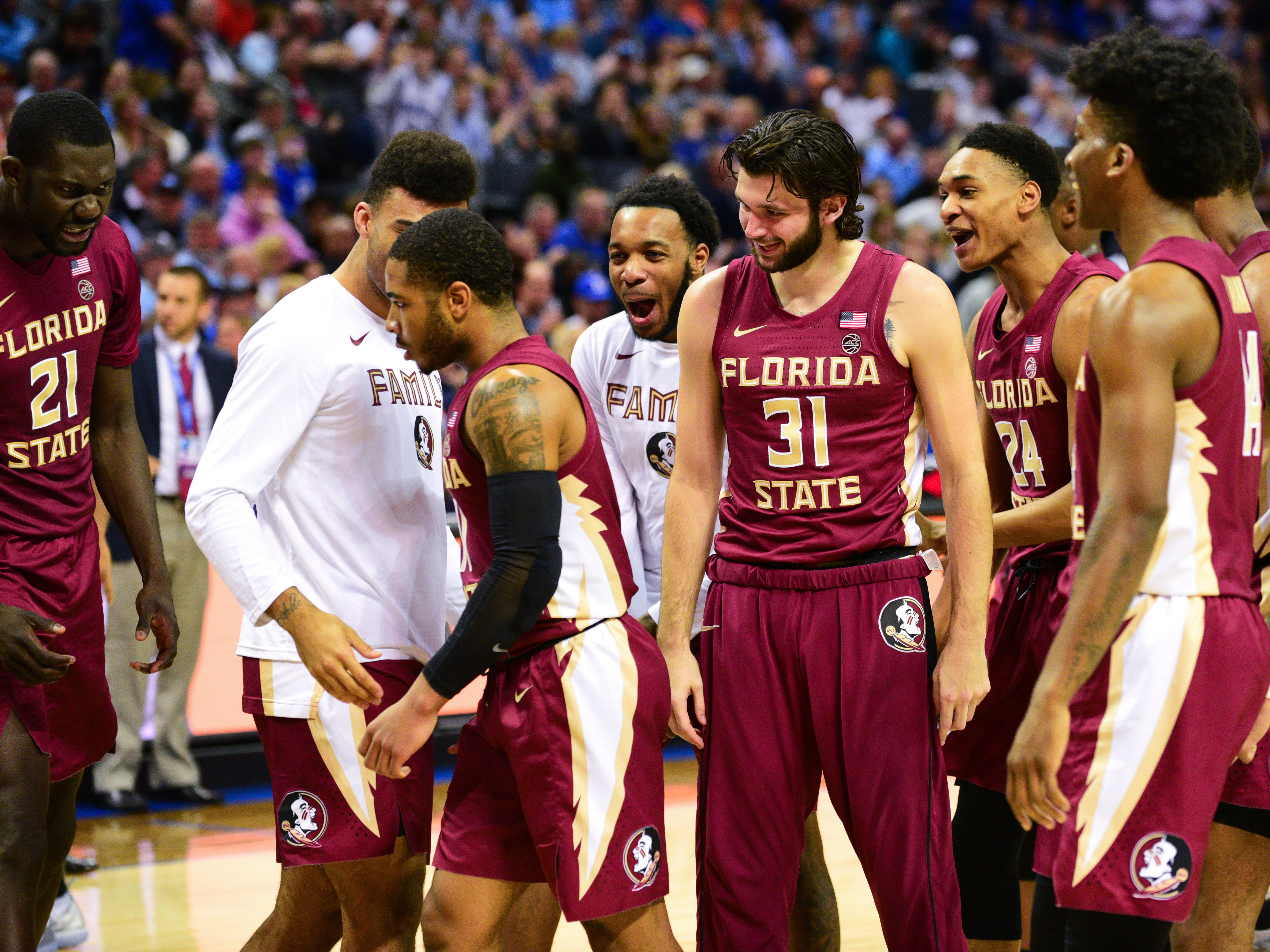 Senior guard David Nichols is greeted with celebration from the Florida State bench at the start of a timeout during the second half of the ACC Tournament Semifinals at the Spectrum Center in Charlotte on Friday.