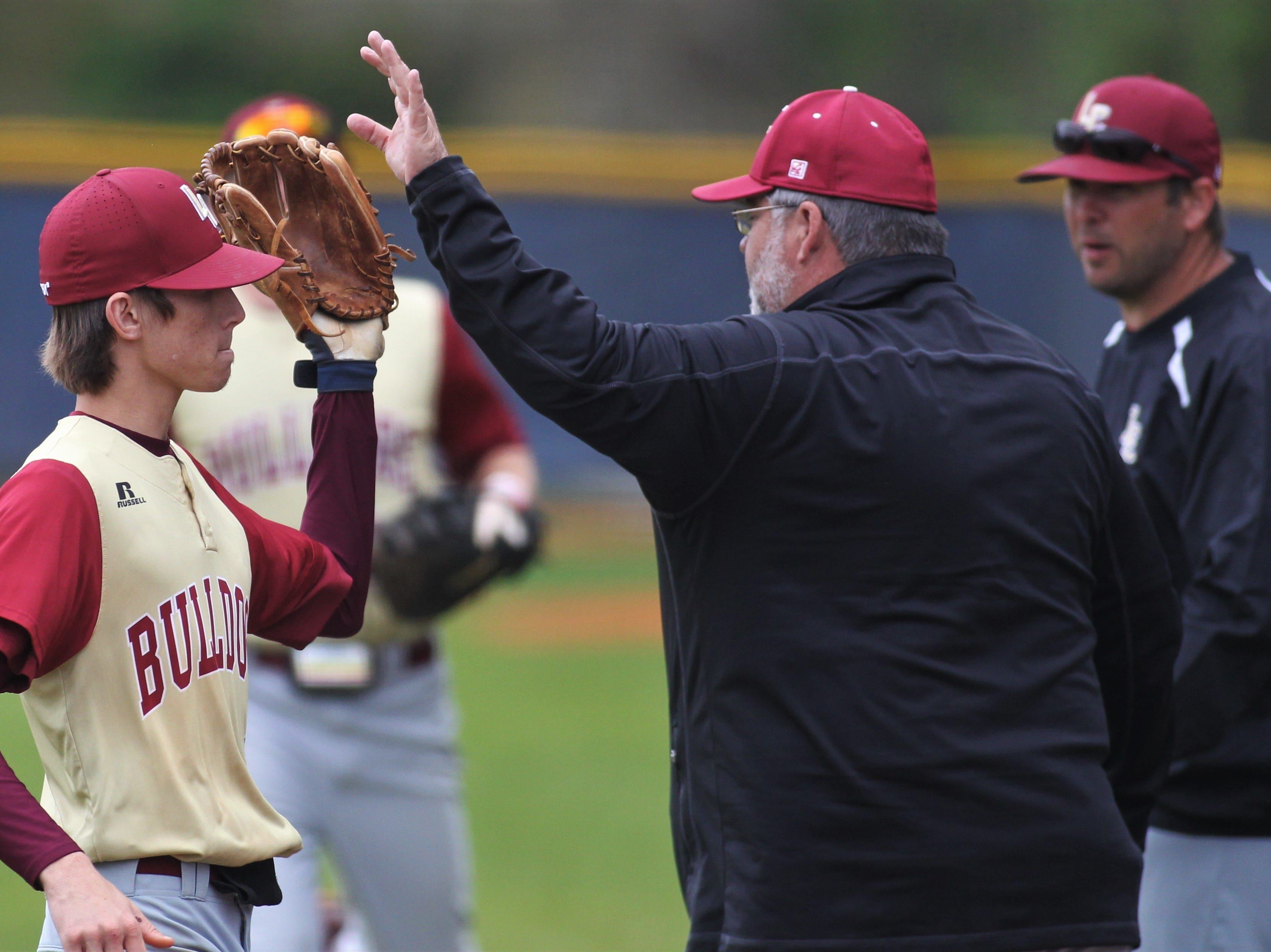 Liberty County starting pitcher Brent Fant is met by an assistant coach after a successful first inning as Liberty County's baseball team went on the road to beat Maclay 8-2 on Saturday, March 16, 2019. The Bulldogs played their first game following their head coach Corey Crum's tragic death six days ago.