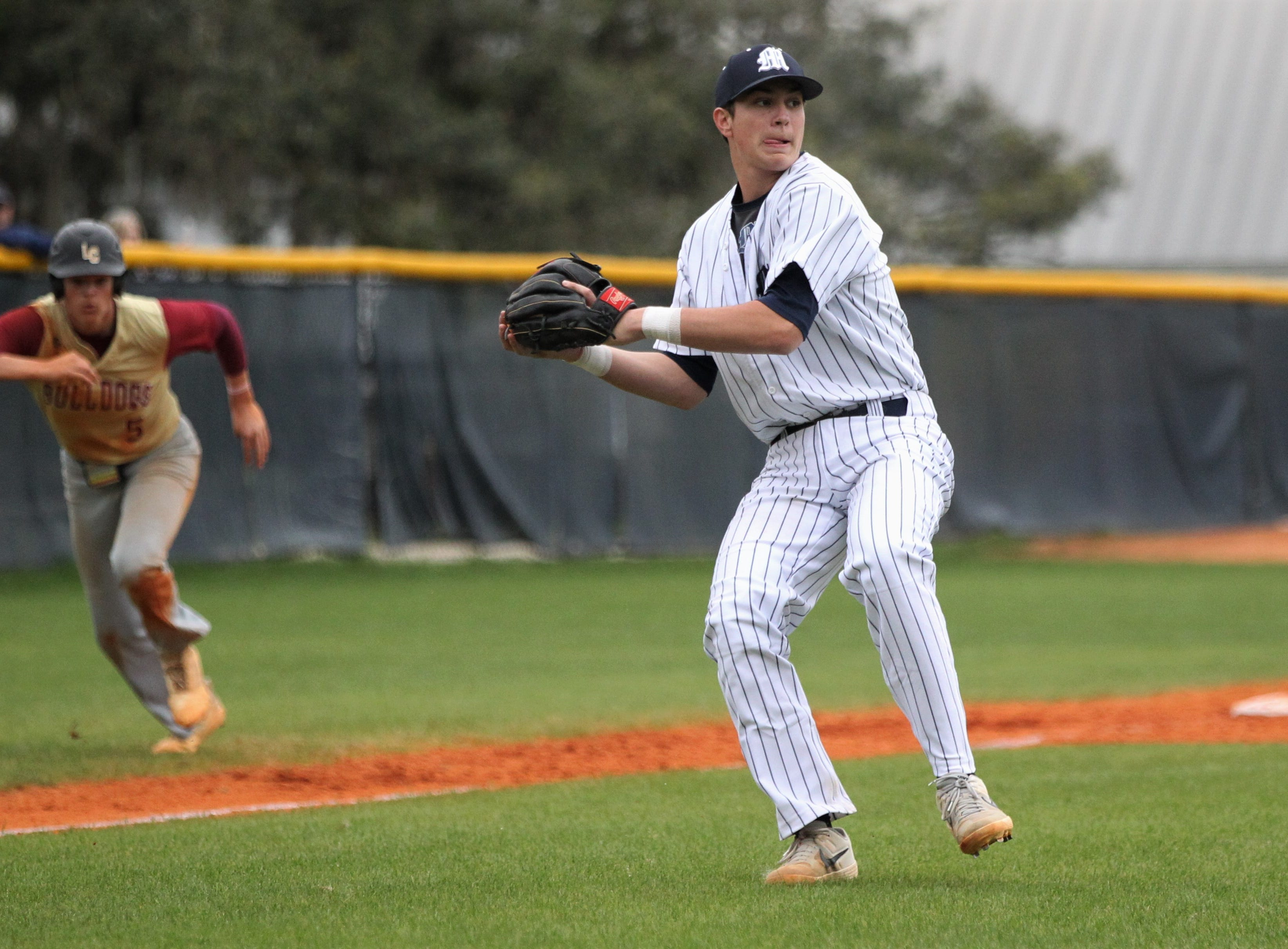 Maclay third baseman Jason Norris fields a bunt and throws to first as Liberty County's baseball team went on the road to beat Maclay 8-2 on Saturday, March 16, 2019. The Bulldogs played their first game following their head coach Corey Crum's tragic death six days ago.
