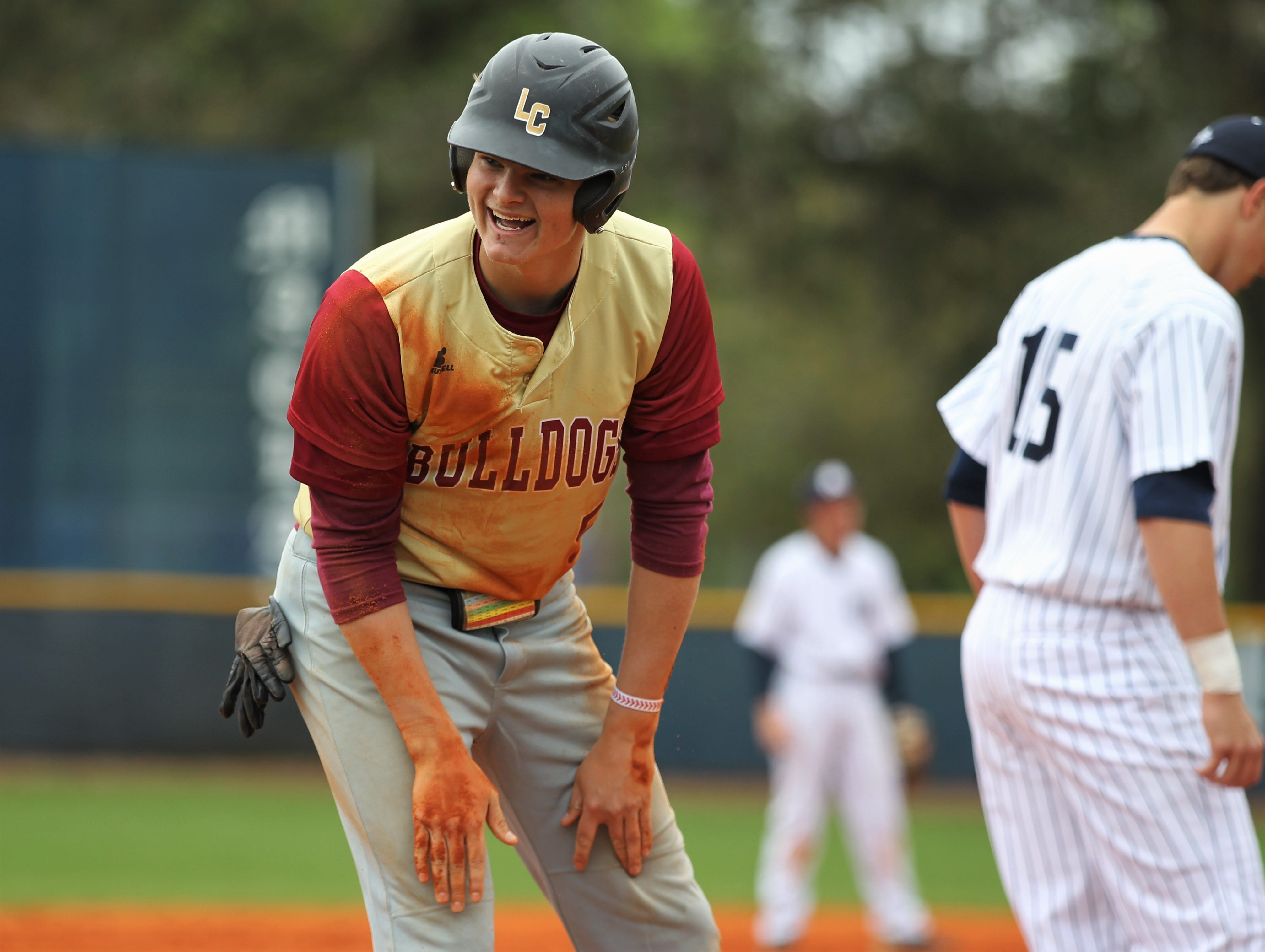Liberty County senior Brice Dillmore smiles at his coach after sliding into third base. Liberty County's baseball team went on the road to beat Maclay 8-2 on Saturday, March 16, 2019. The Bulldogs played their first game following their head coach Corey Crum's tragic death six days ago.