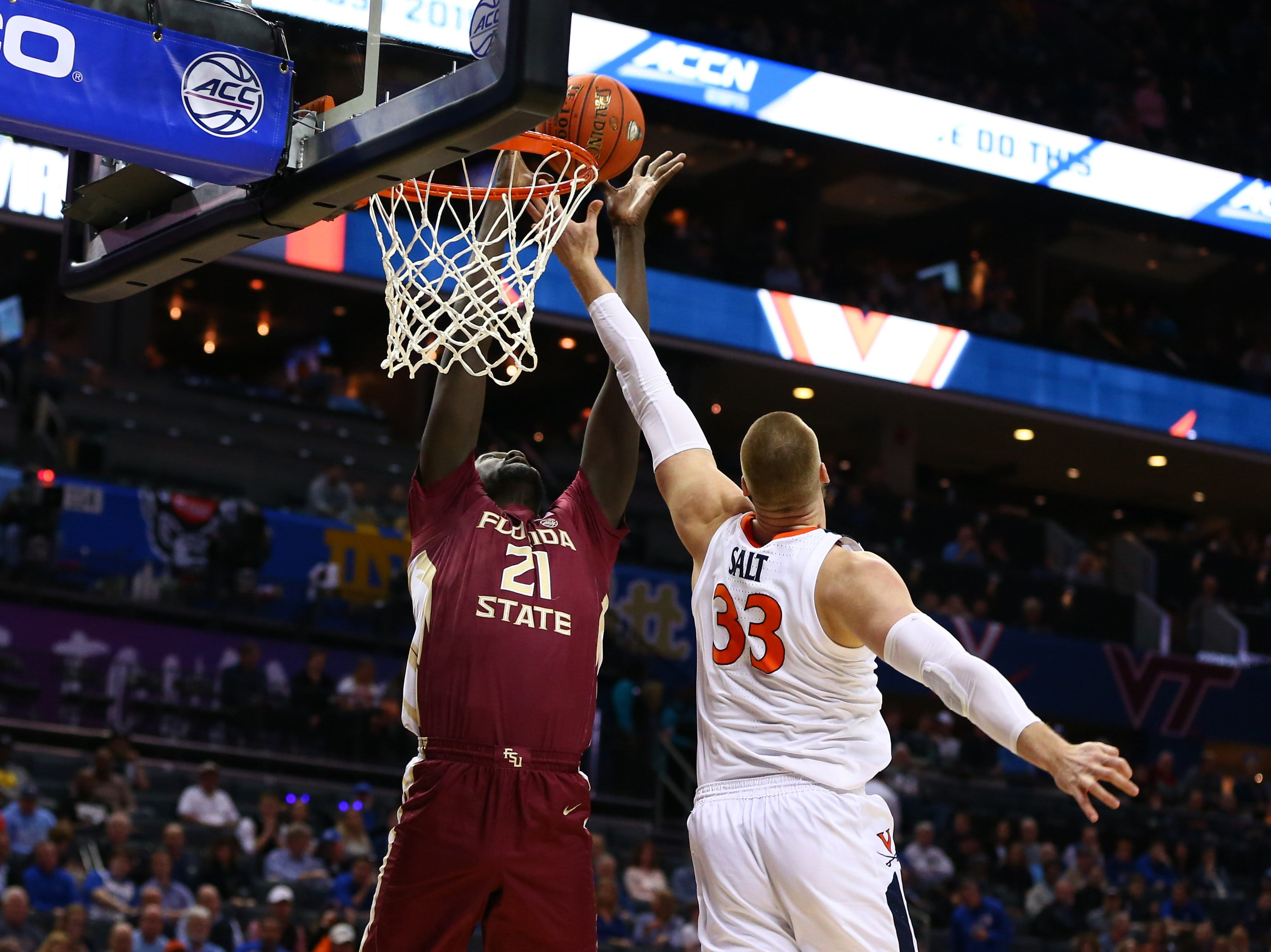 Mar 15, 2019; Charlotte, NC, USA; Florida State Seminoles center Christ Koumadje (21) goes up to dunk against Virginia Cavaliers center Jack Salt (33) in the first half in the ACC conference tournament at Spectrum Center. Mandatory Credit: Jeremy Brevard-USA TODAY Sports