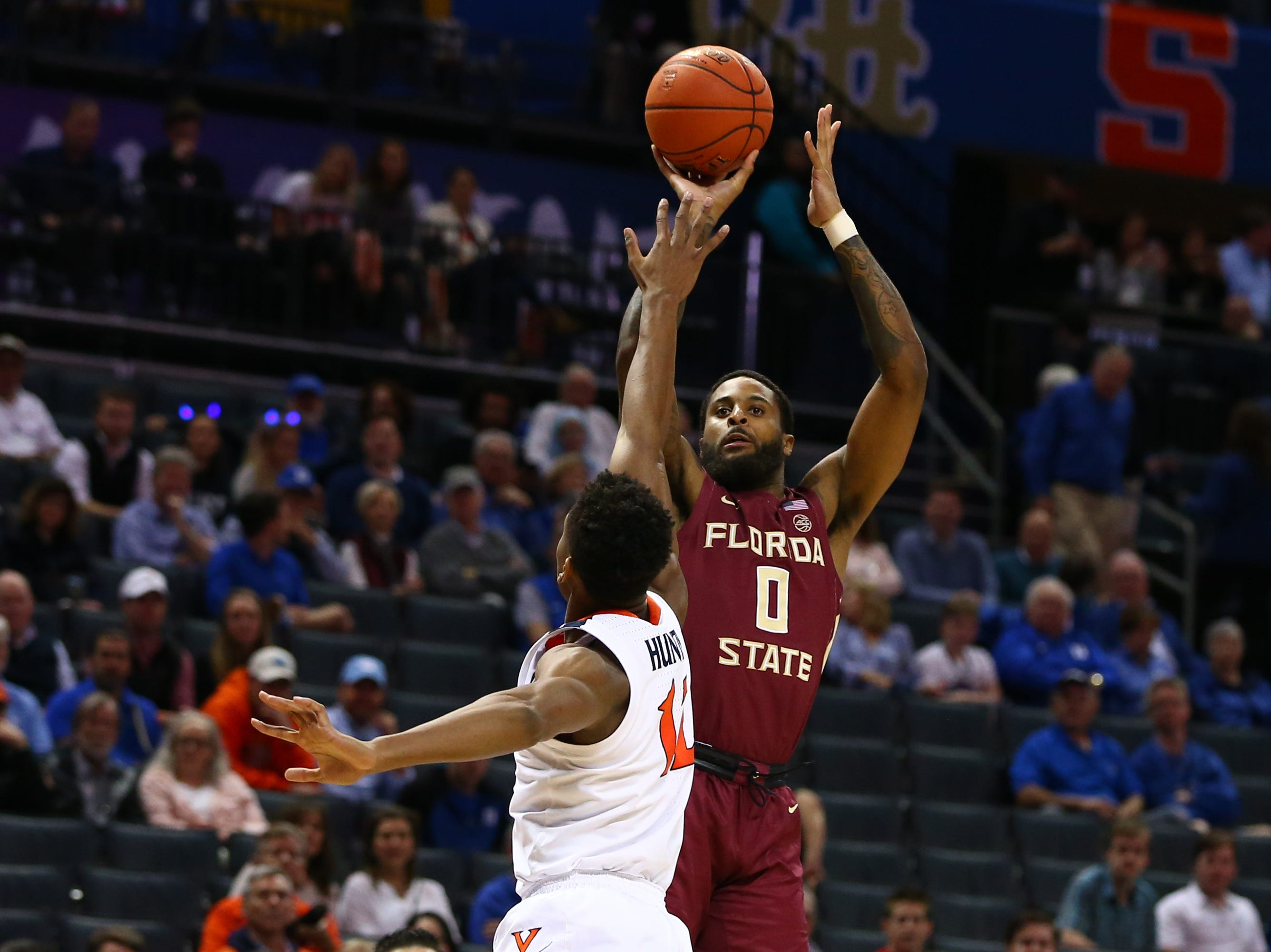 Mar 15, 2019; Charlotte, NC, USA; Florida State Seminoles forward Phil Cofer (0) shoots the ball against Virginia Cavaliers guard De'Andre Hunter (12) in the first half in the ACC conference tournament at Spectrum Center. Mandatory Credit: Jeremy Brevard-USA TODAY Sports