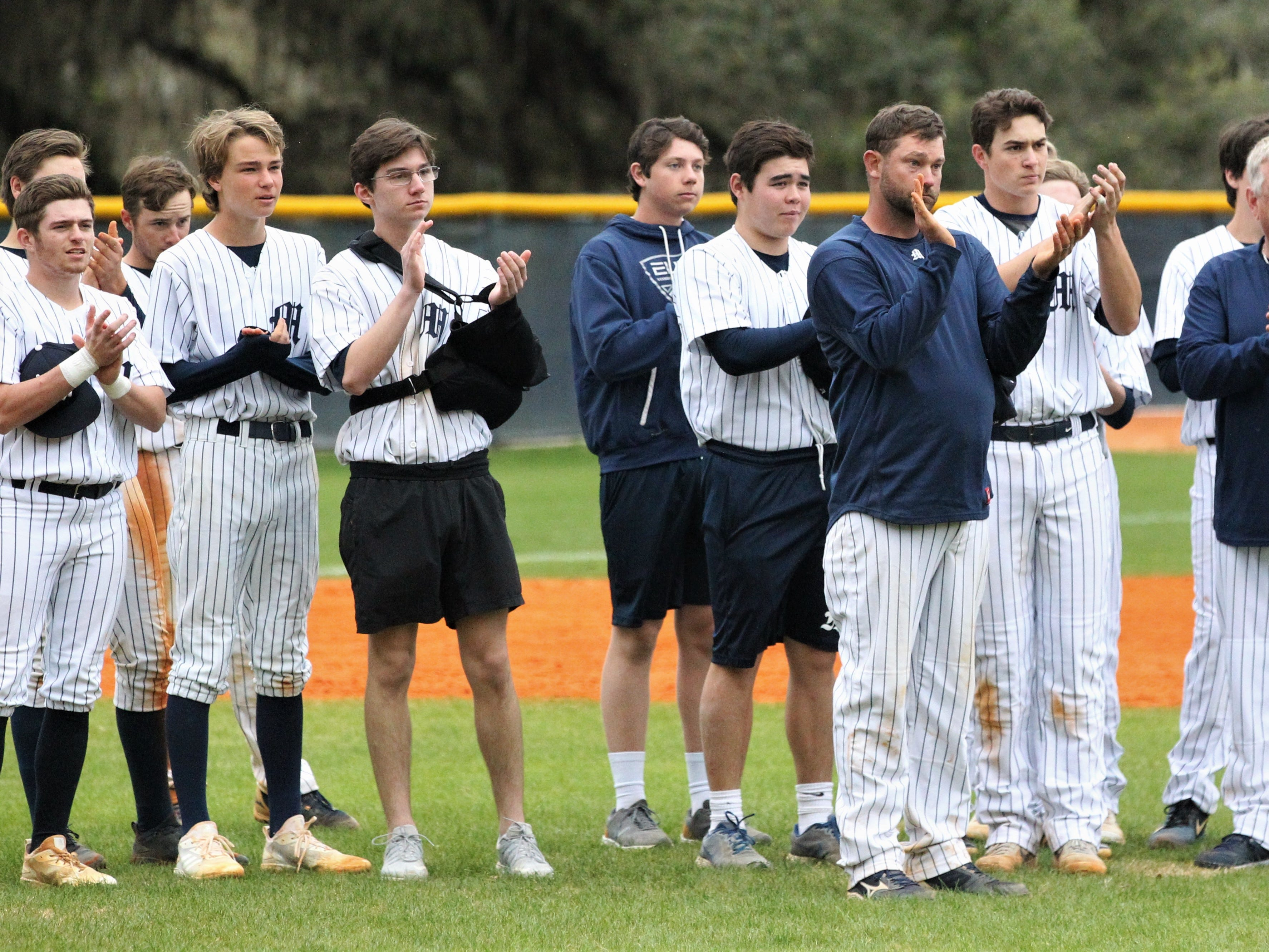 Maclay baseball coach Drew Sherrod leads his team in applause of Liberty County's baseball team, which won 8-2 just six days after its head coach's tragic death.