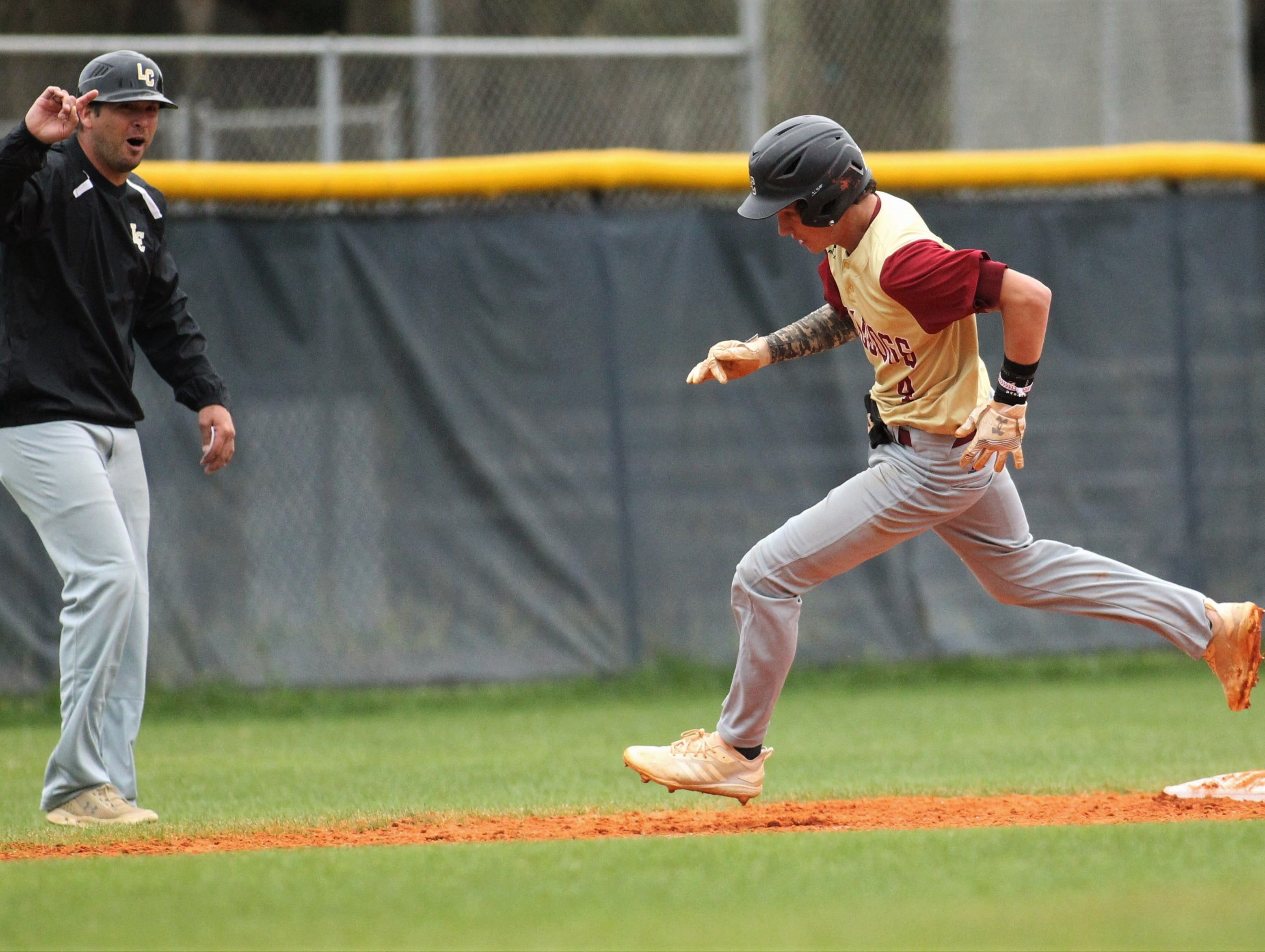 Liberty County's Austin Waller races around third to score a run, as directed by coach Mannie Stafford, as Liberty County's baseball team went on the road to beat Maclay 8-2 on Saturday, March 16, 2019. The Bulldogs played their first game following their head coach Corey Crum's tragic death six days ago.