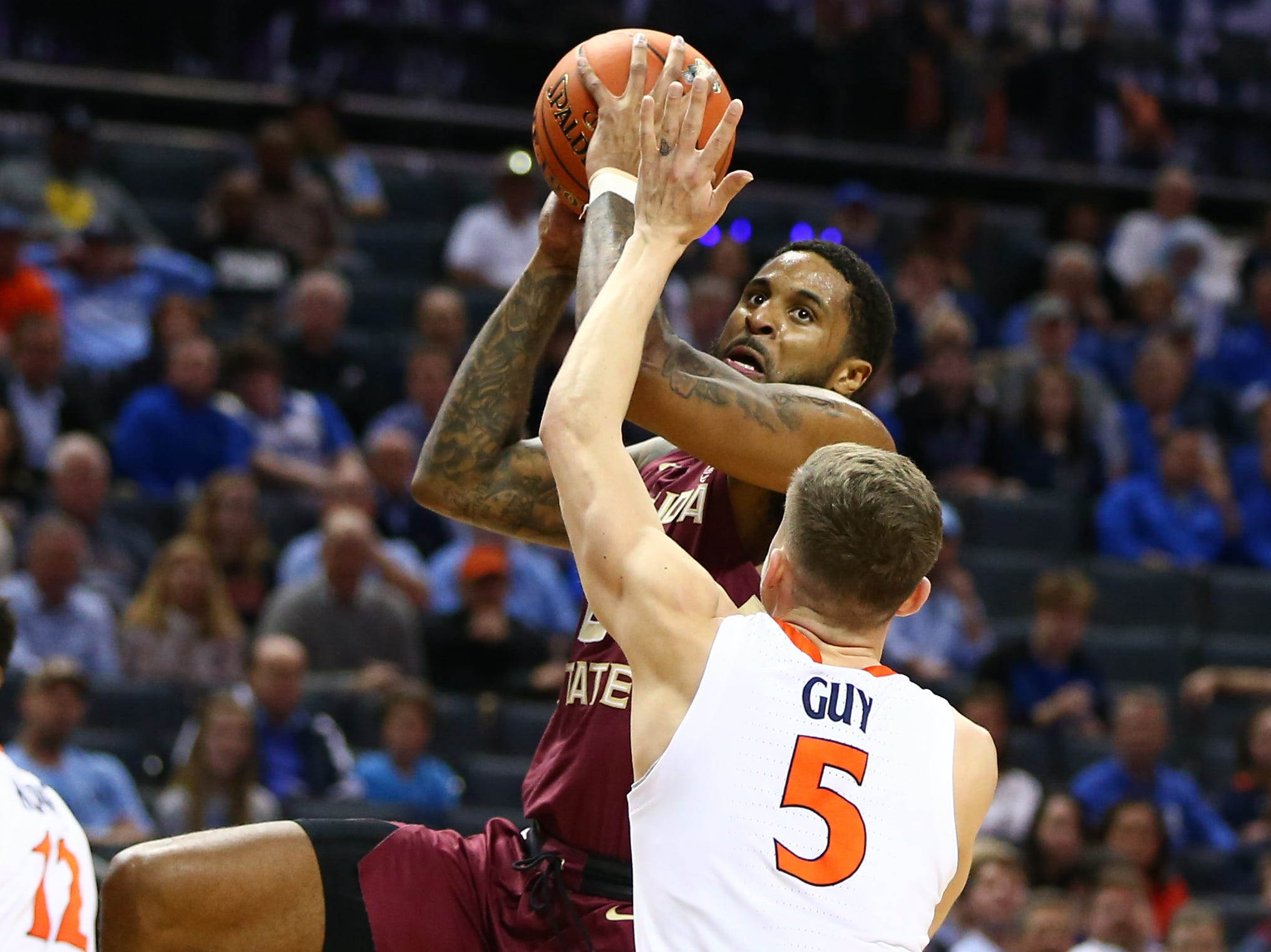 Mar 15, 2019; Charlotte, NC, USA; Florida State Seminoles forward Phil Cofer (0) shoots the ball against Virginia Cavaliers guard Kyle Guy (5) in the first half in the ACC conference tournament at Spectrum Center. Mandatory Credit: Jeremy Brevard-USA TODAY Sports