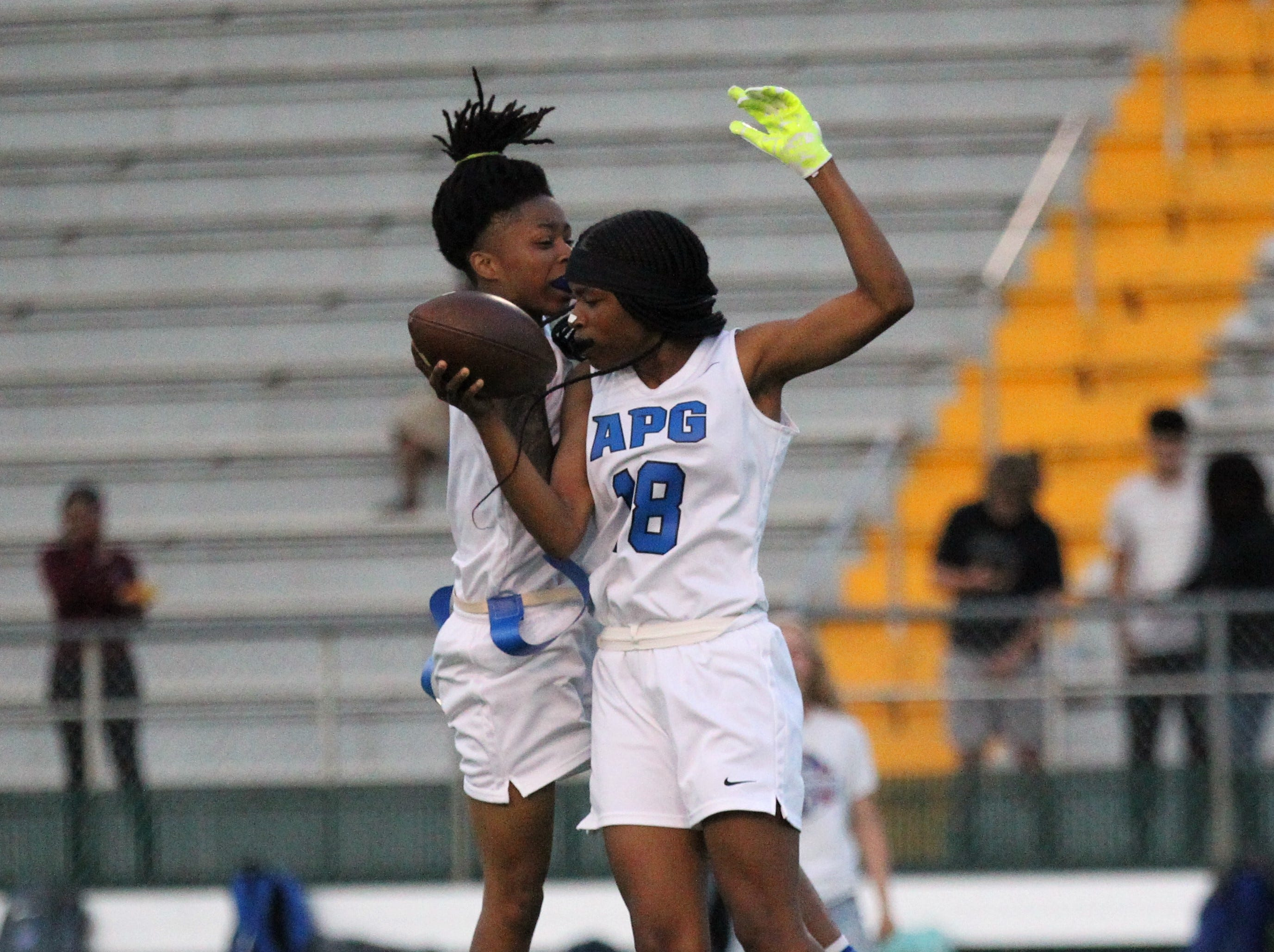Godby's Gisele Jones (18) and Toni McClain chest bump after a big play as Godby's flag football team beat Lincoln 25-6 at Gene Cox Stadium on March 14, 2019.