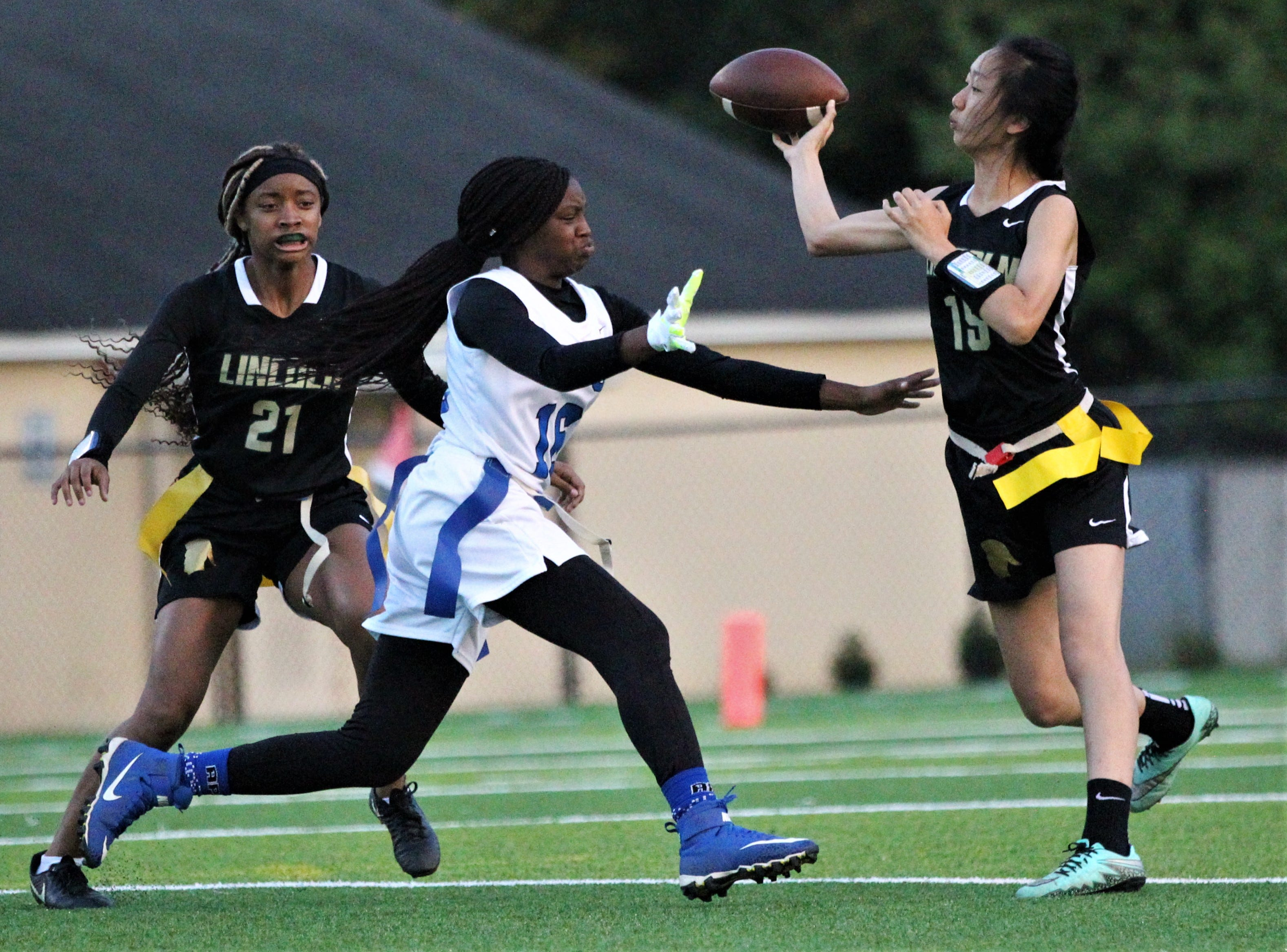 Lincoln quarterback Ivy Zheng throws a pass before Godby's Essence Nobles reaches her flags as the Cougars beat the Trojans 25-6 at Gene Cox Stadium on March 14, 2019.