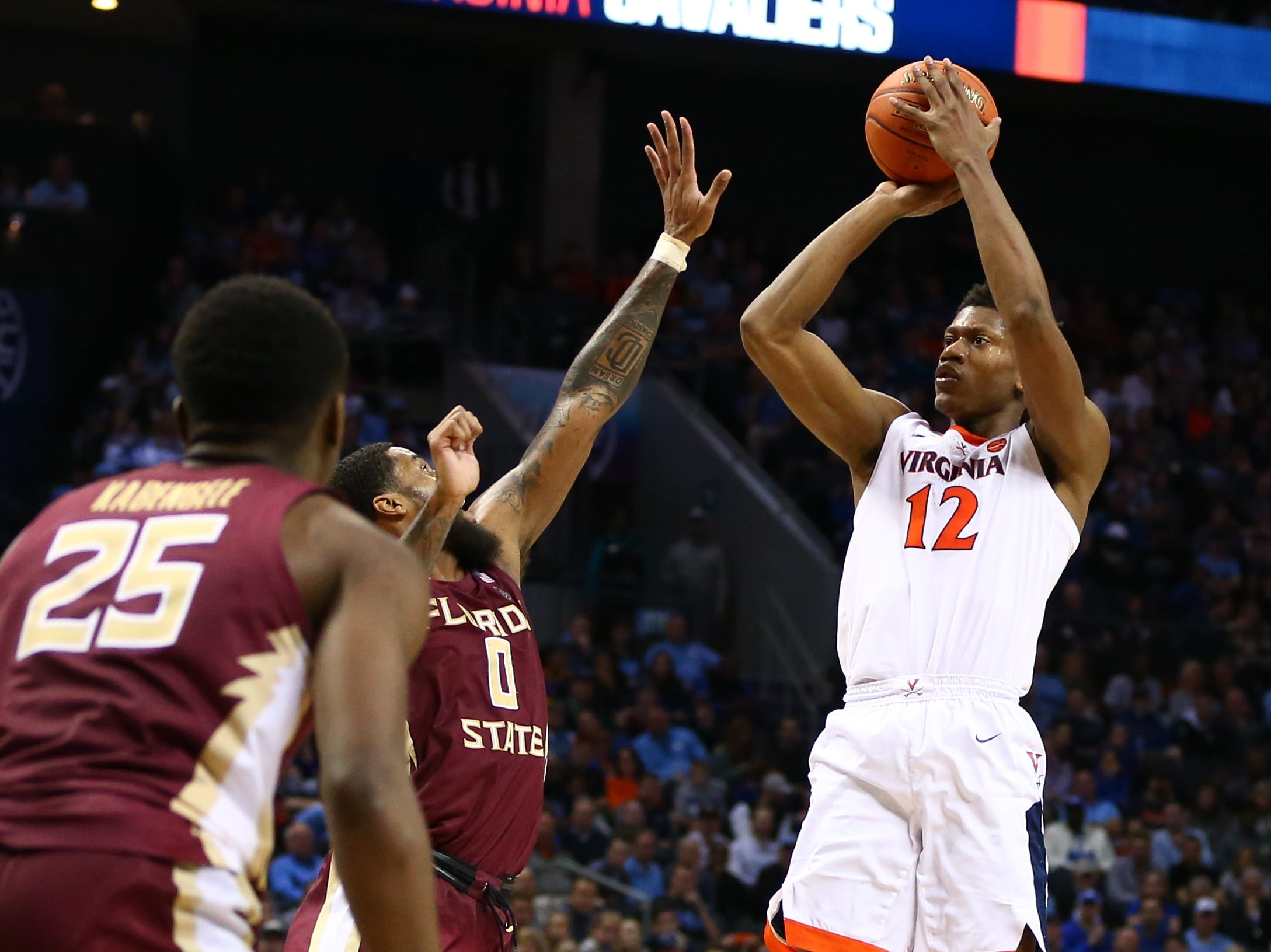 Mar 15, 2019; Charlotte, NC, USA; Virginia Cavaliers guard De'Andre Hunter (12) shoots the ball against Florida State Seminoles forward Phil Cofer (0) in the second half in the ACC conference tournament at Spectrum Center. Mandatory Credit: Jeremy Brevard-USA TODAY Sports