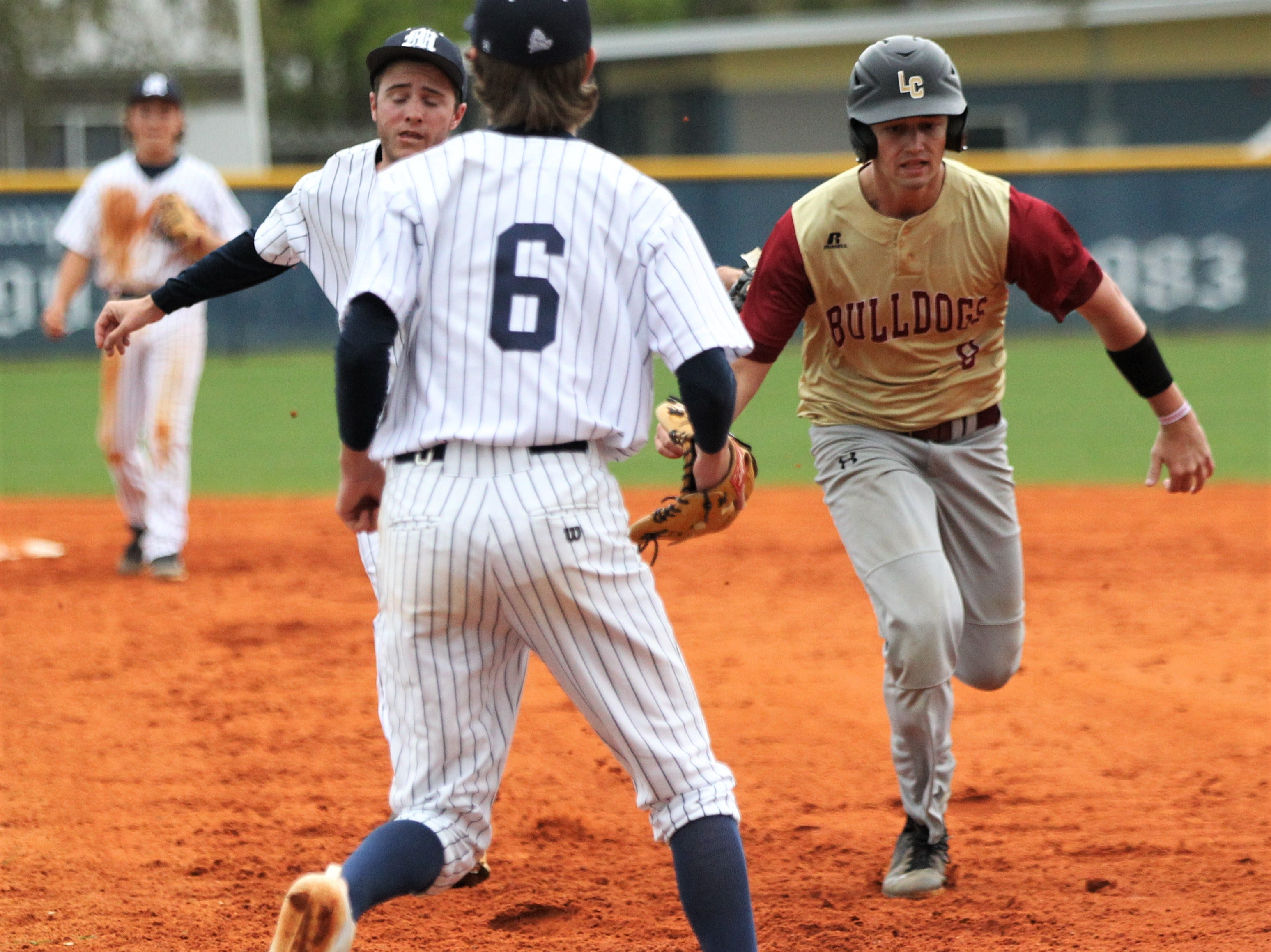 Maclay's Grant Harrison tags out Liberty County's Hunter Sanford in a rundown as Liberty County's baseball team went on the road to beat Maclay 8-2 on Saturday, March 16, 2019. The Bulldogs played their first game following their head coach Corey Crum's tragic death six days ago.