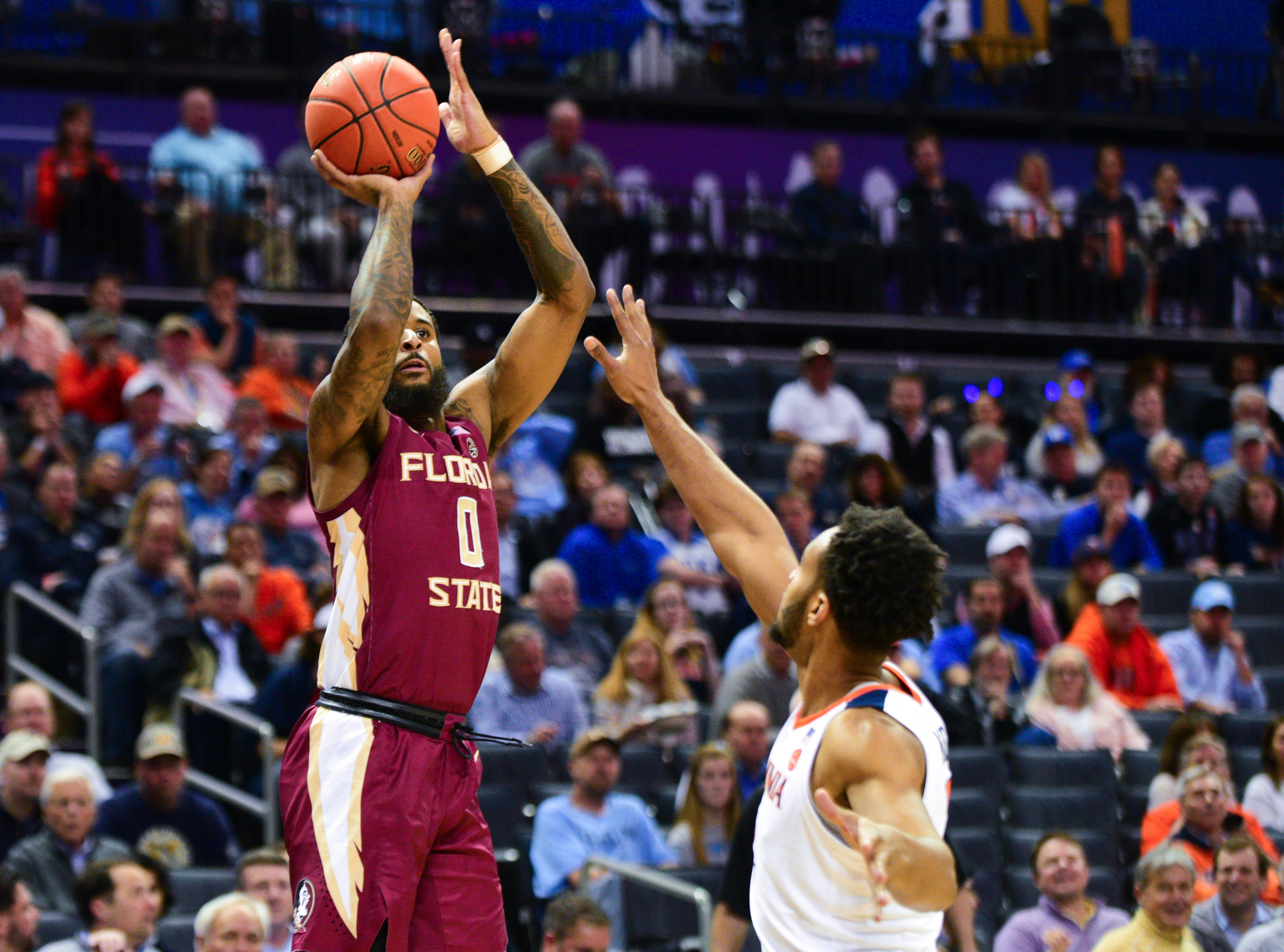 Redshirt senior forward Phil Cofer, left, shoots for three during the first half of the ACC Tournament Semifinals at the Spectrum Center in Charlotte on Friday.