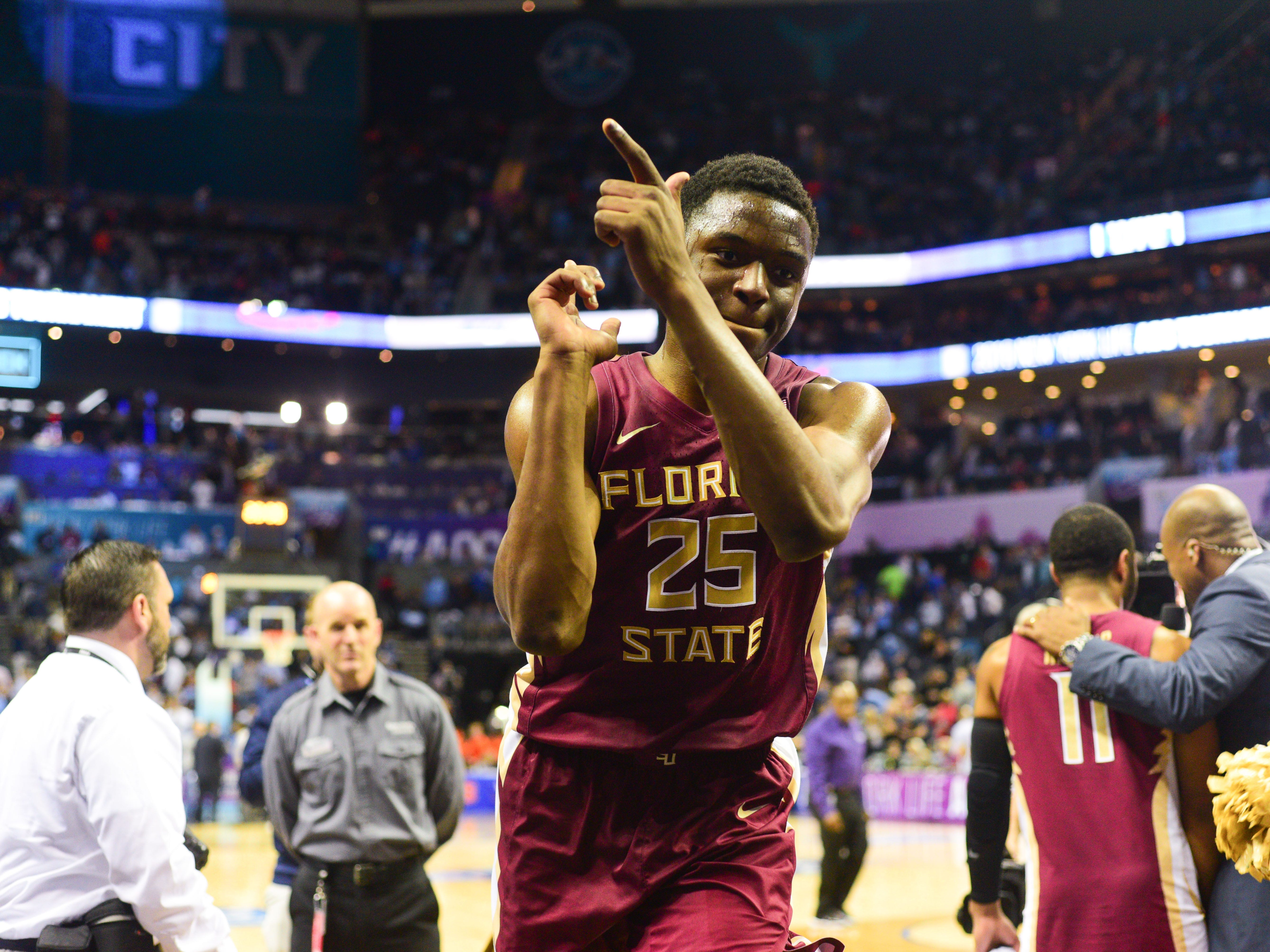 Redshirt sophomore guard Mfiondu Kabengele gestures finger guns to cheering Florida State fans after the Seminoles 69-59 victory in the ACC Tournament Semifinal game at the Spectrum Center on Friday.