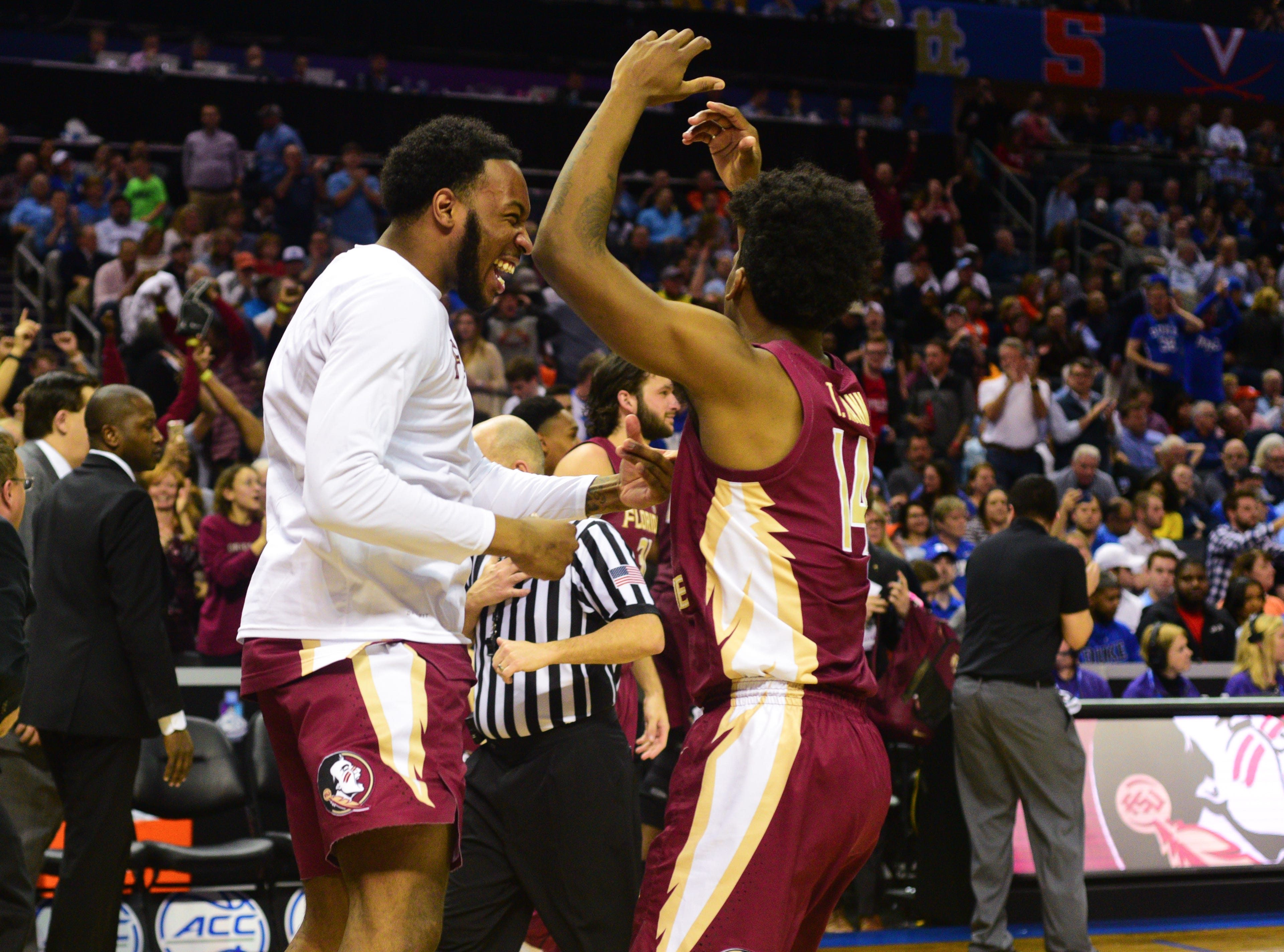 Senior guards PJ Savoy, left, and Terance Mann, right, celebrate after Florida State's 69-59 victory over Virginia in the ACC Tournament Semifinal game at the Spectrum Center on Friday.