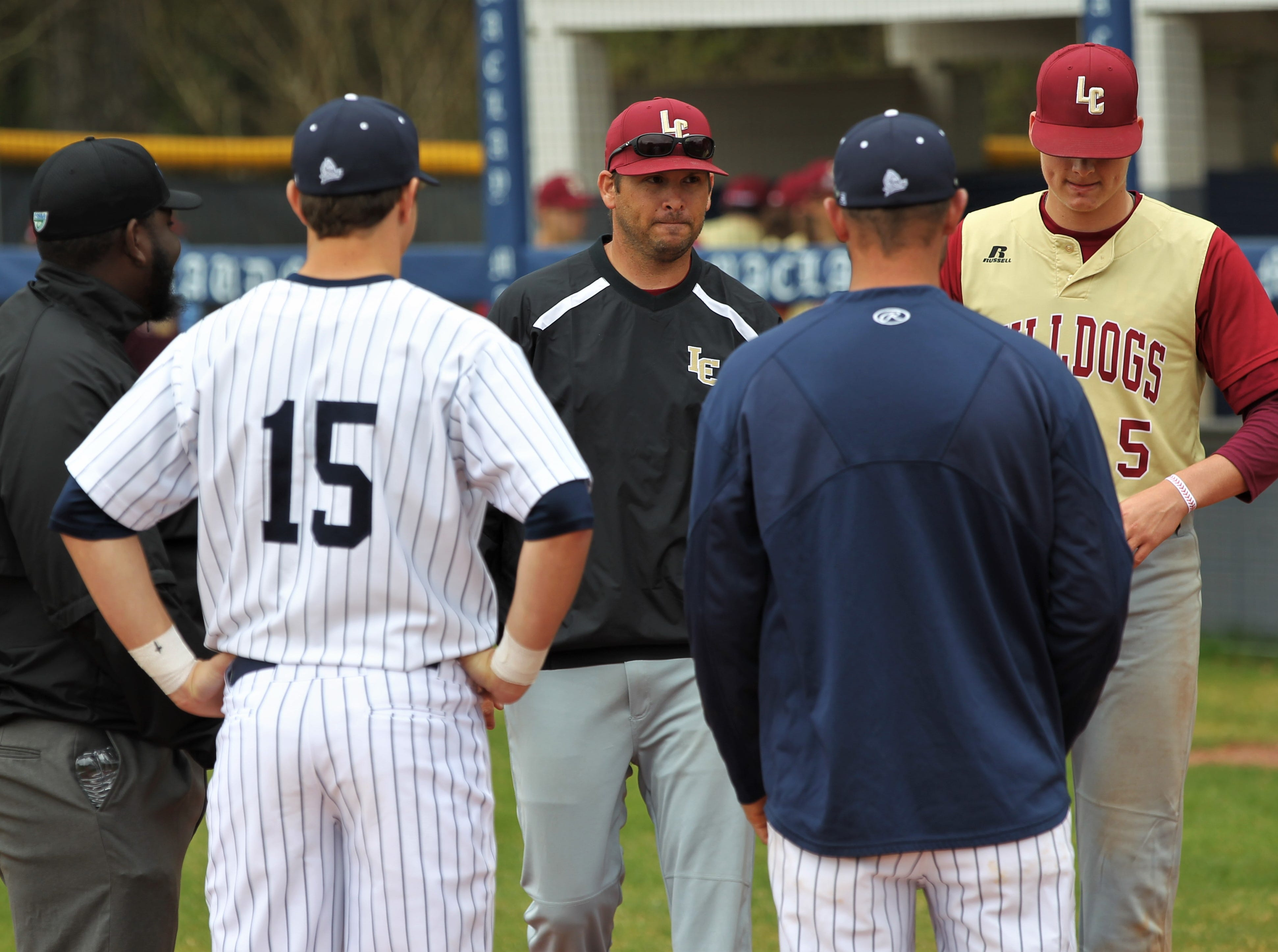 Liberty County coach Mannie Stafford and senior Brice Dillmore (5) meet Maclay coach Drew Sherrod and senior Jason Norris (15) at home plate before a game. Liberty County's baseball team went on the road to beat Maclay 8-2 on Saturday, March 16, 2019. The Bulldogs played their first game following their head coach Corey Crum's tragic death six days ago.
